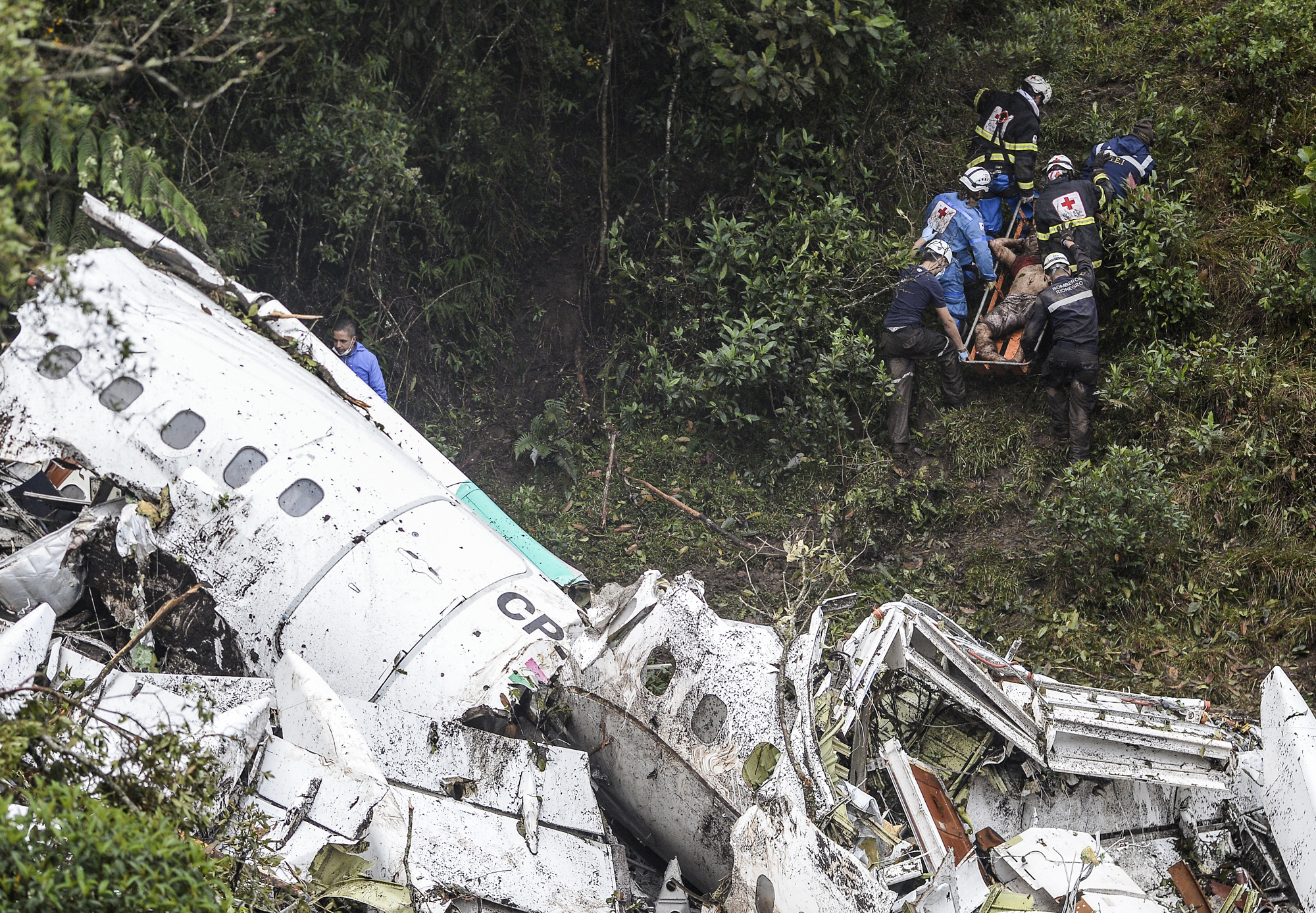 TOPSHOT - EDITORS NOTE: Graphic content / Rescue and forensic teams recover the bodies of victims of the LAMIA airlines charter that crashed in the mountains of Cerro Gordo, municipality of La Union, Colombia, on November 29, 2016 carrying members of the Brazilian football team Chapecoense Real. A charter plane carrying the Brazilian football team crashed in the mountains in Colombia late Monday, killing as many as 75 people, officials said. / AFP / STR / Raul ARBOLEDA / GRAPHIC CONTENT (Photo credit should read RAUL ARBOLEDA/AFP/Getty Images)