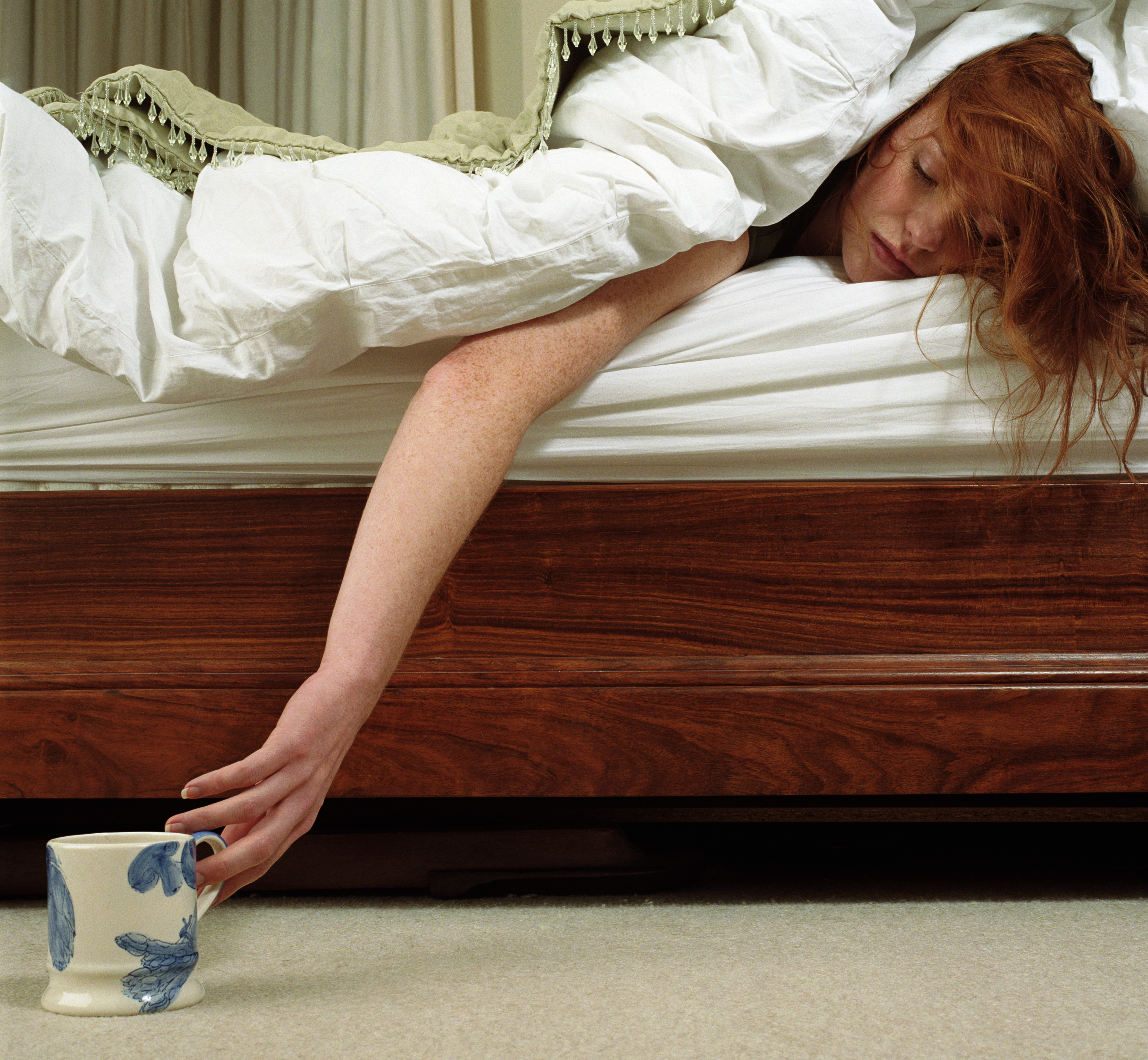 Woman lying in bed reaching for mug on carpet, eyes closed
