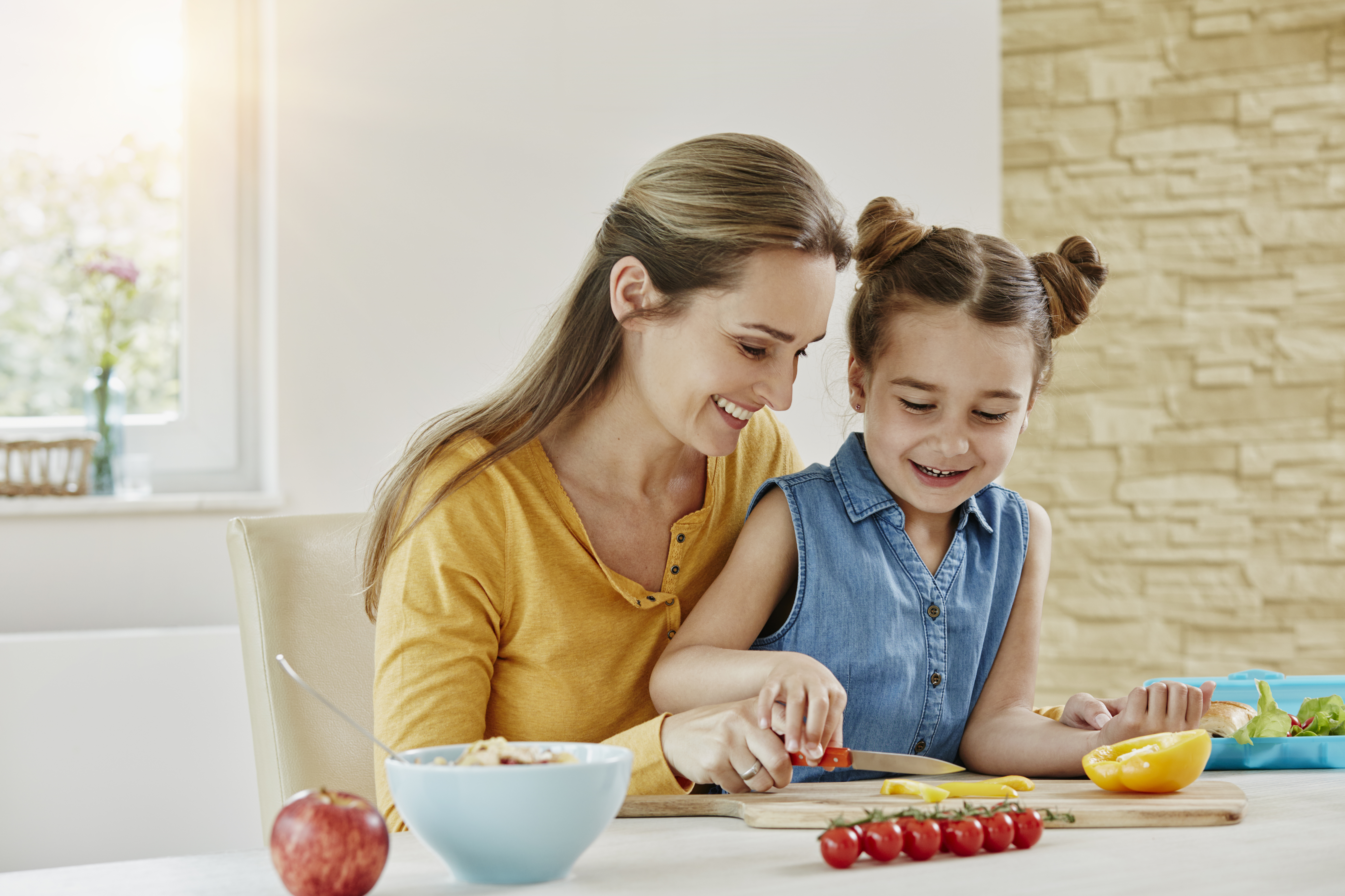 Happy mother with daughter at home cutting vegetables