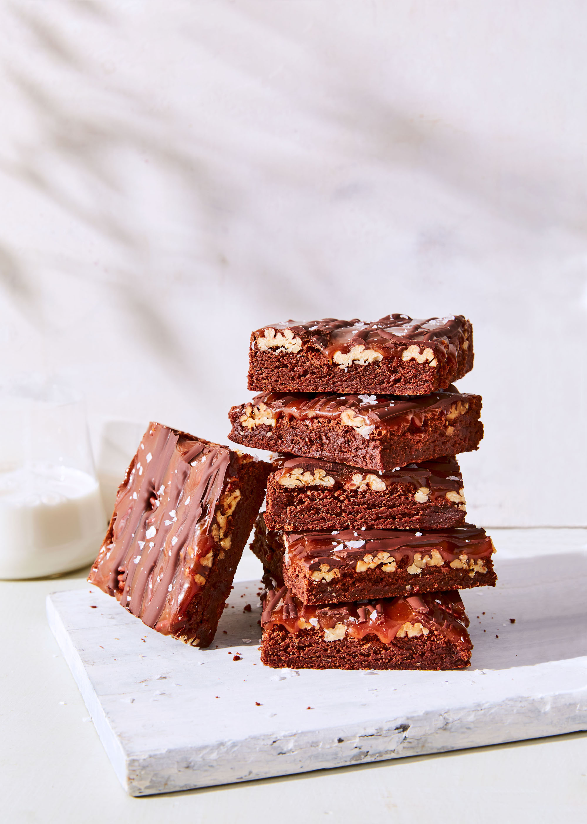 fudgy turtle brownies stacked on cutting board