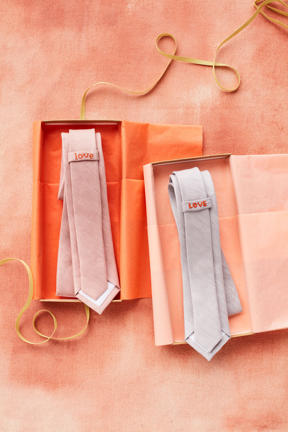 two neckties in orange boxes with love embroidered on them