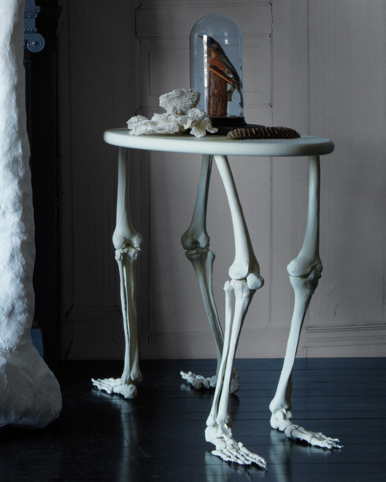 Frankenstein saw inspiration in the most grotesque of scavenging—here, we took a note from his book and constructed a bare-bones table decoration. The table legs are legs indeed—store-bought faux bones. To make it, trim the thigh bones: Use saw to cut the legs to 1 inch less than the desired table height (to account for tabletop). Next, stabilize the knees: Take each leg apart at the knee; unscrew the hardware, and remove the kneecap. Connect shin bone to thighbone with one double-threaded screw (3/16-by-3 inches). Lastly, stabilize the ankles: Position one foot so it rests flat on the floor, and generously squeeze epoxy into the hinge that makes the ankle flex. Repeat with the remaining legs. Let it dry and cure overnight at least before moving onto the next step. Attach the legs to the table: Decide where you want the legs, and drill pilot holes through tabletop. Place each leg underneath the pilot hole, then screw to attach. Put putty over the screws, and let it dry. Sand until smooth. Paint the tabletop a skeletal white.