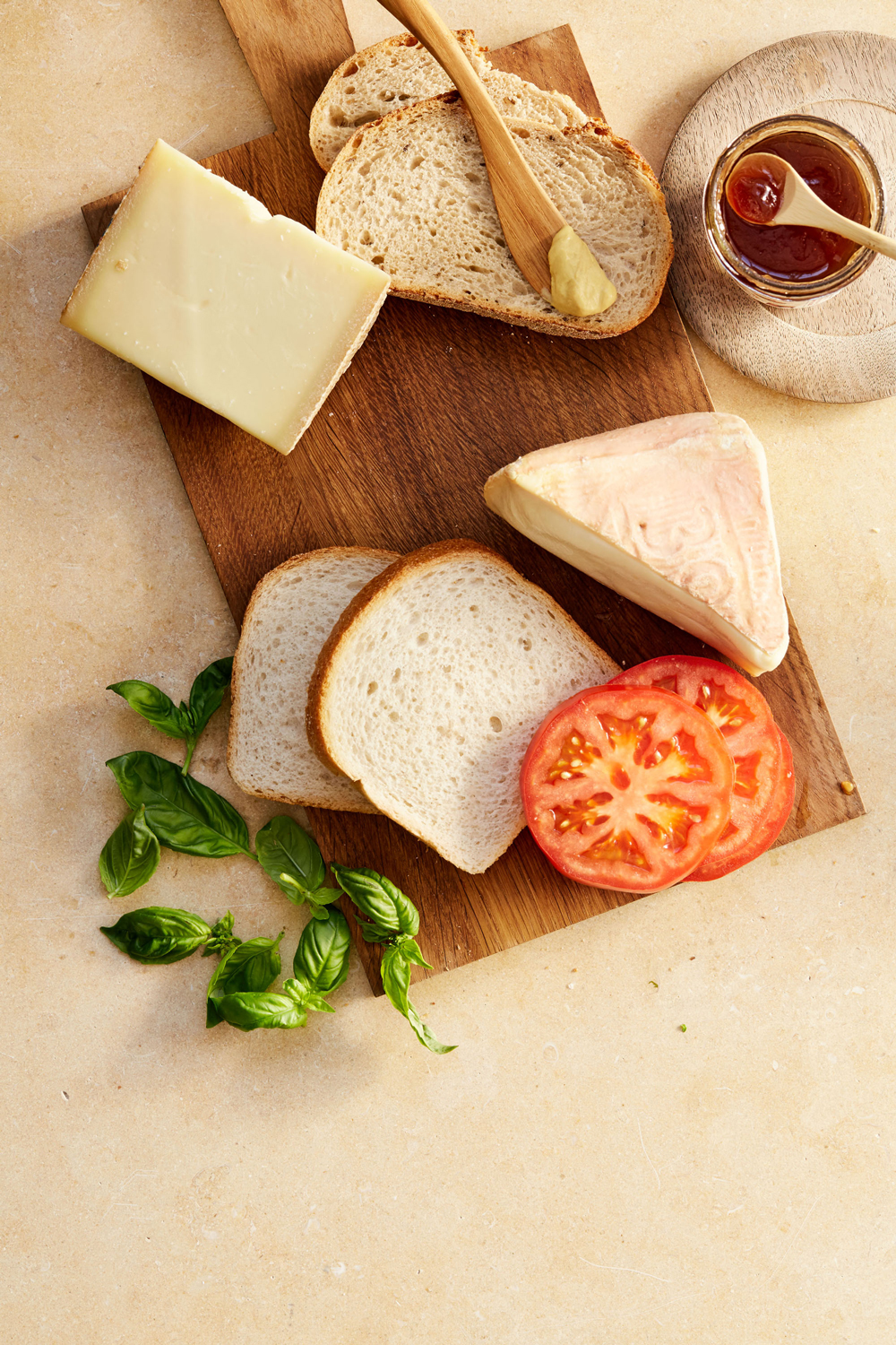 bread butter cheese and tomatoes on cutting board