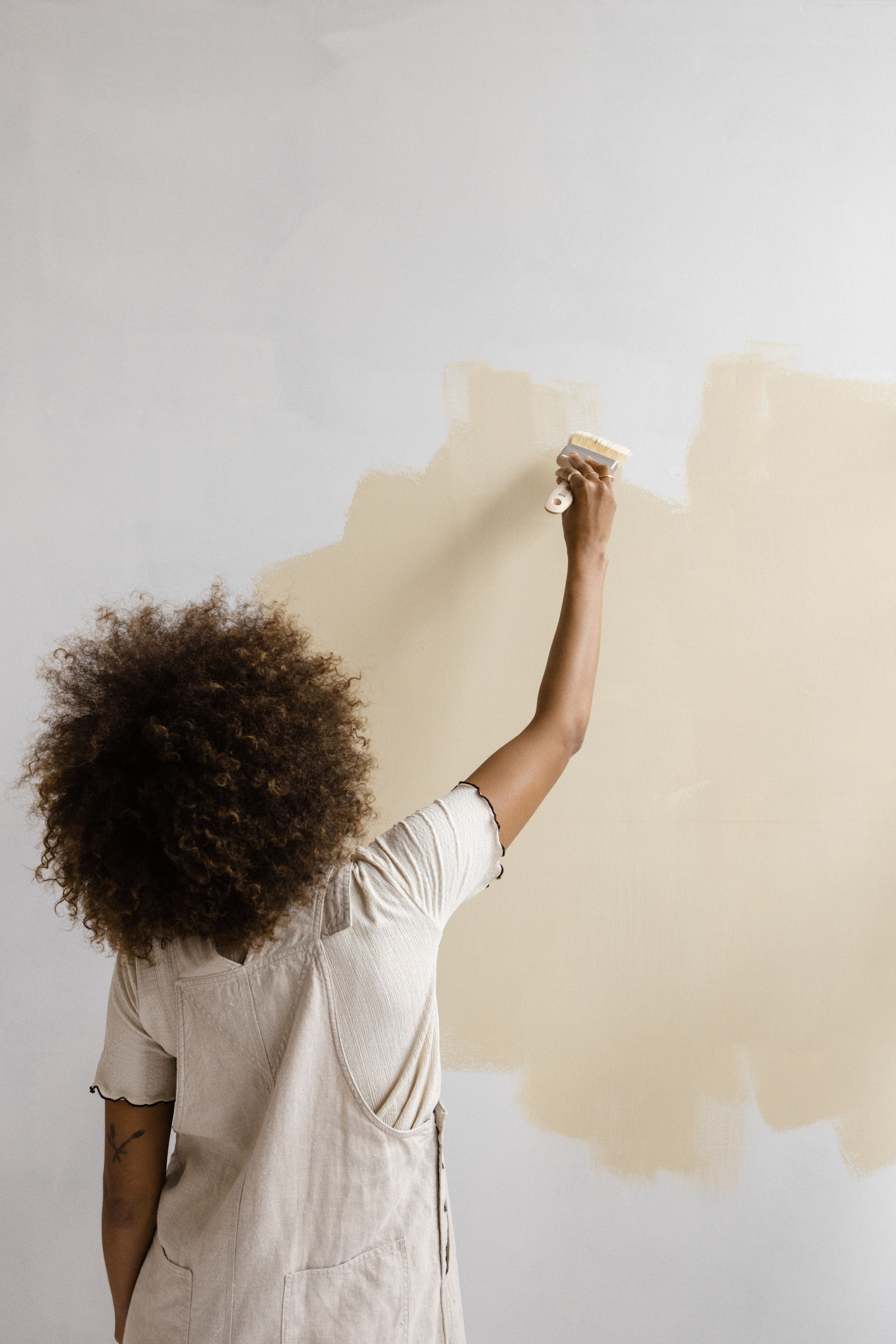 woman painting beige onto wall