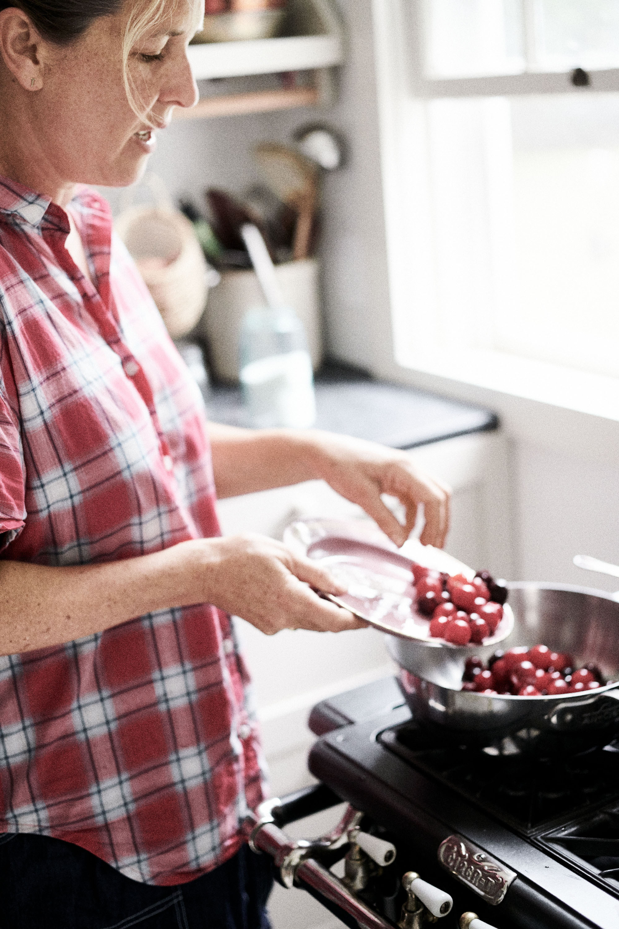 woman pouring cherries into metal bowl