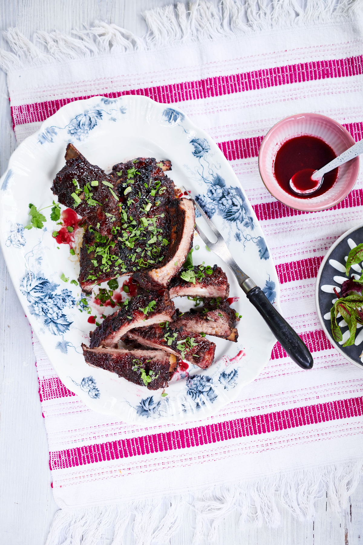 sour-cherry and five spice lacquered ribs garnished with scallions and cilantro