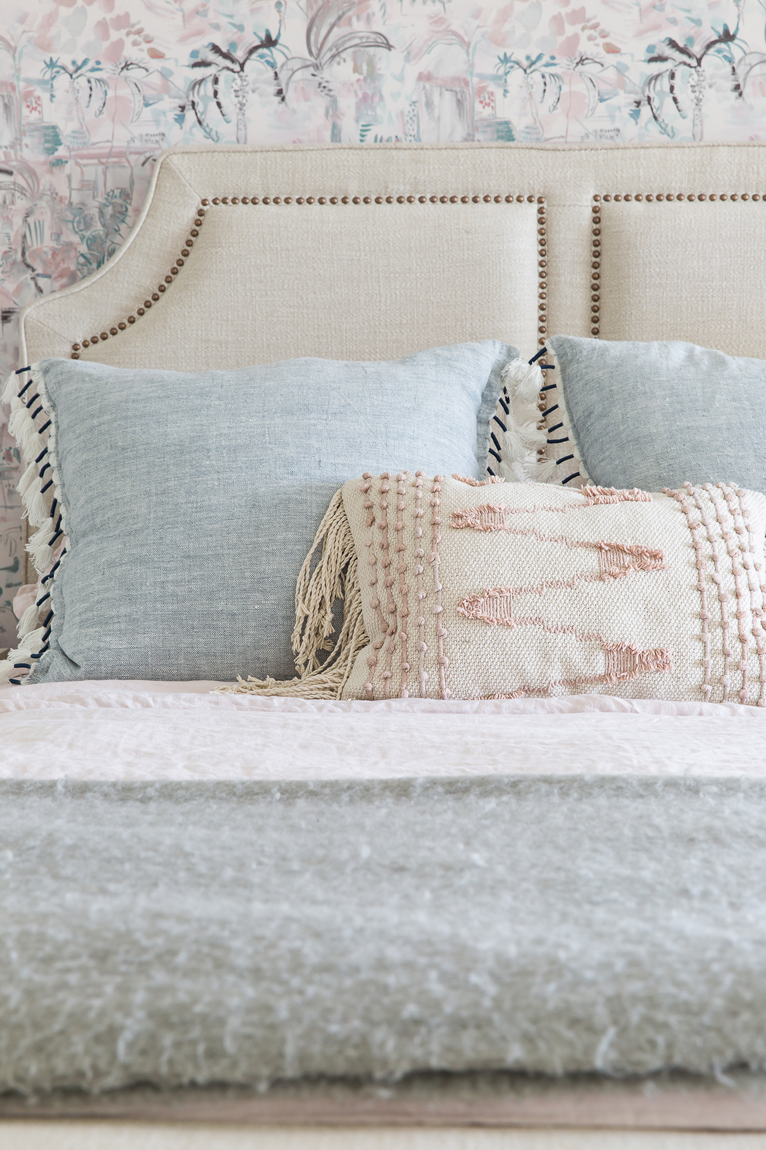 blue-gray and pink pastel pillows on bed