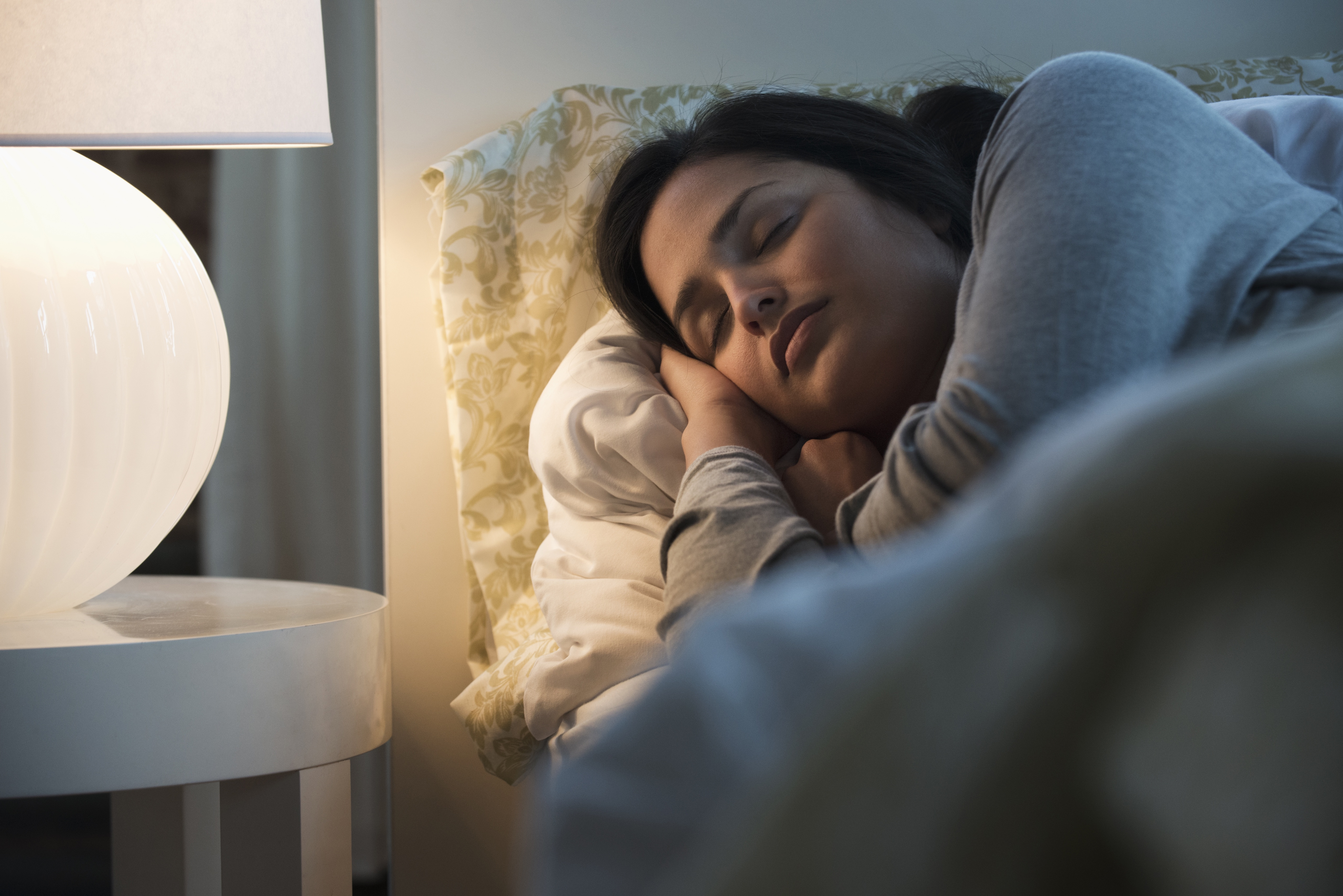 Woman sleeping in bed with light on