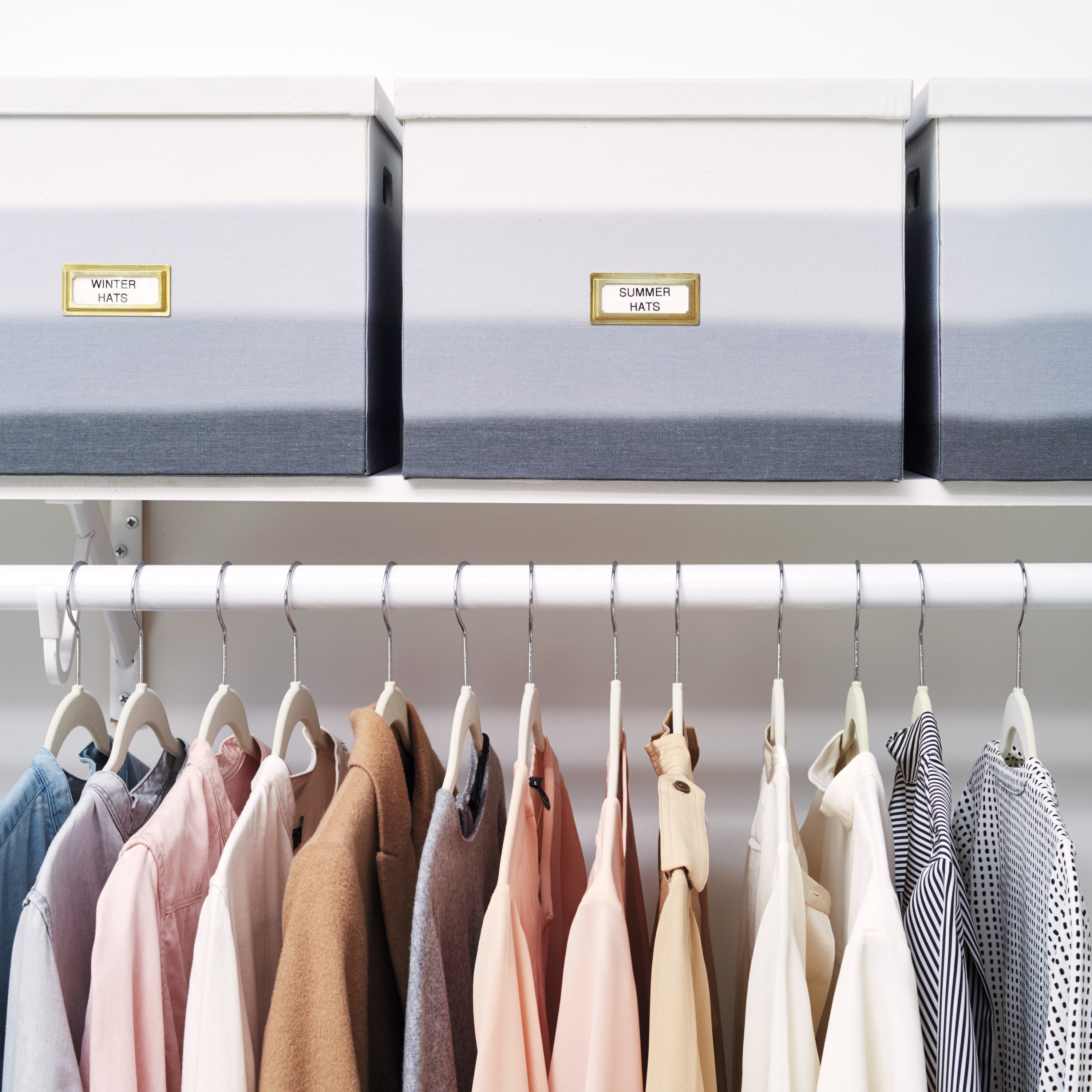 hanging clothes in closet with labeled boxes