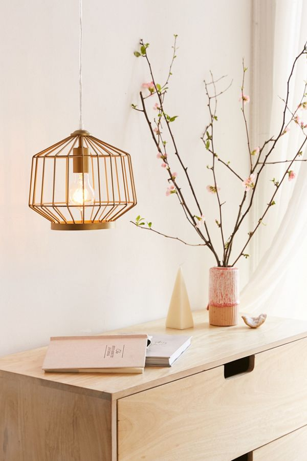 "Don't let the harsh dorm overheads be your only source of light. ""Plug-in pendant lights are everything,"" Richardson says. ""Find a really cool one or two and hang those babies."" They'll add coziness and major ambience to your space. We like this chic brass light from Urban Outfitters."