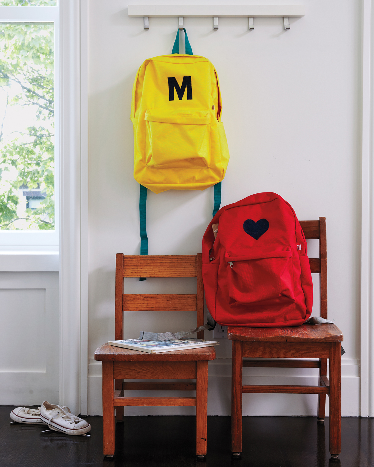 personalized backpacks hanging in a mudroom