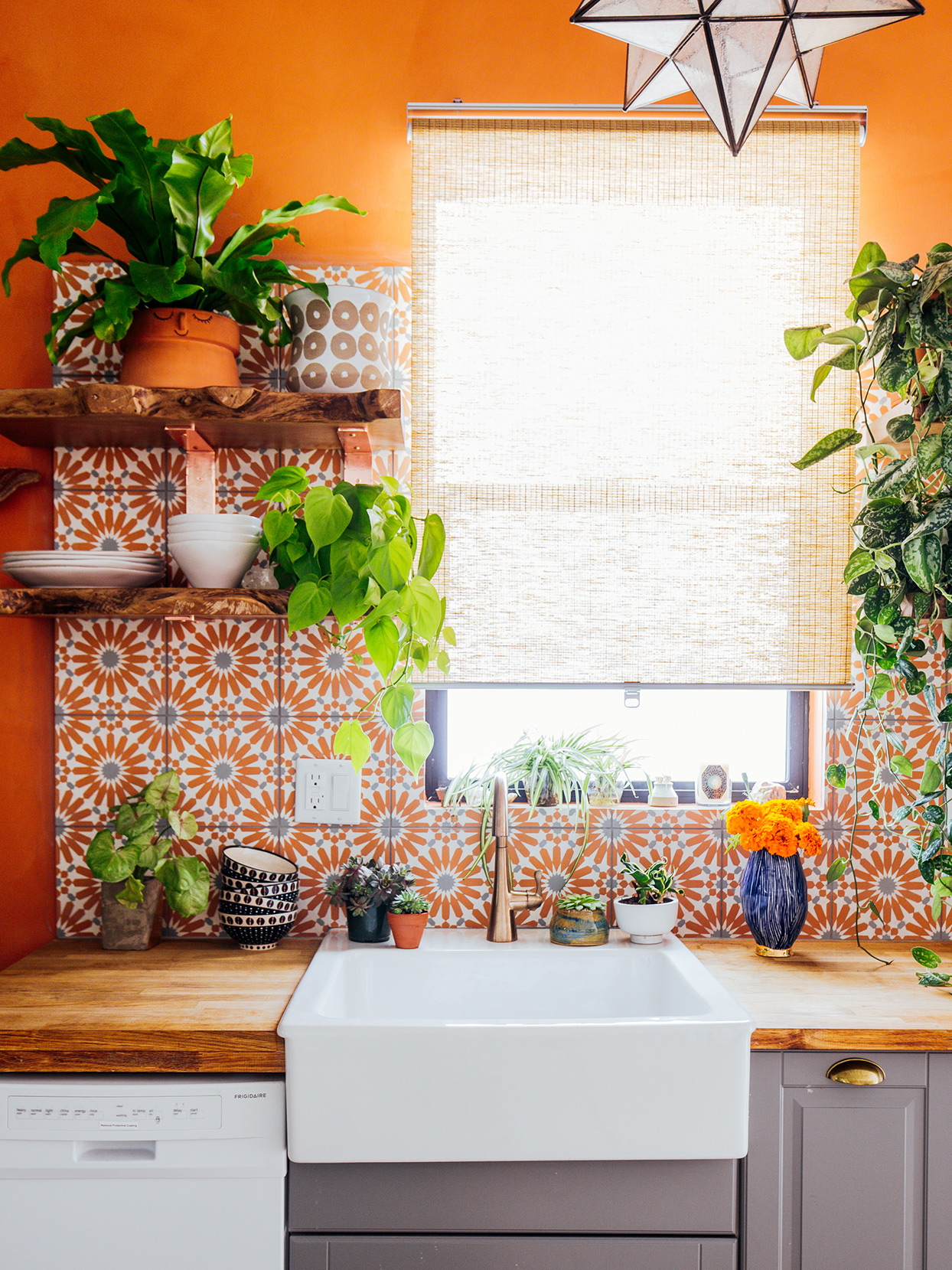 orange geometric floral backsplash tiles in bright kitchen