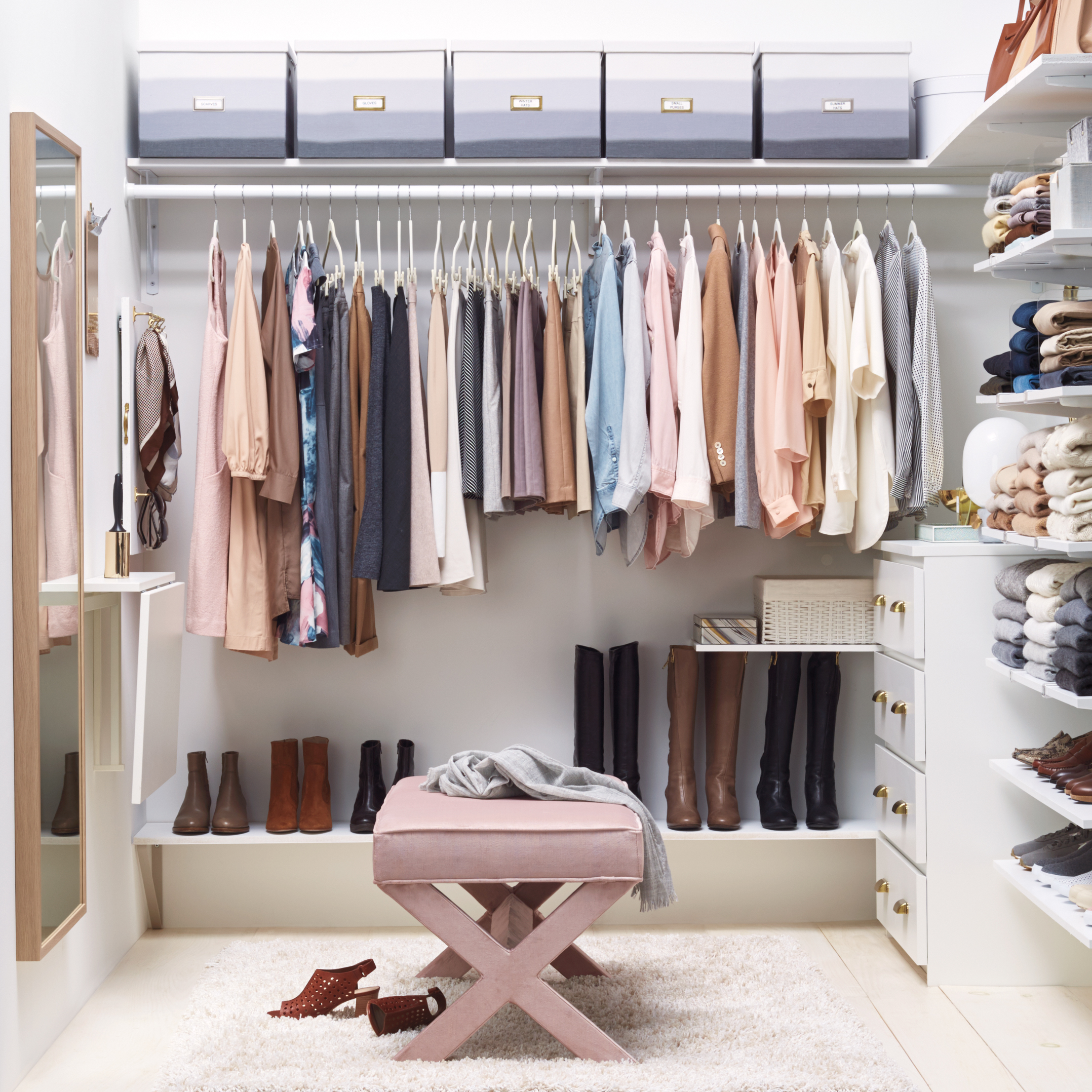 white walk-in closet with pastel-colored clothes hanging