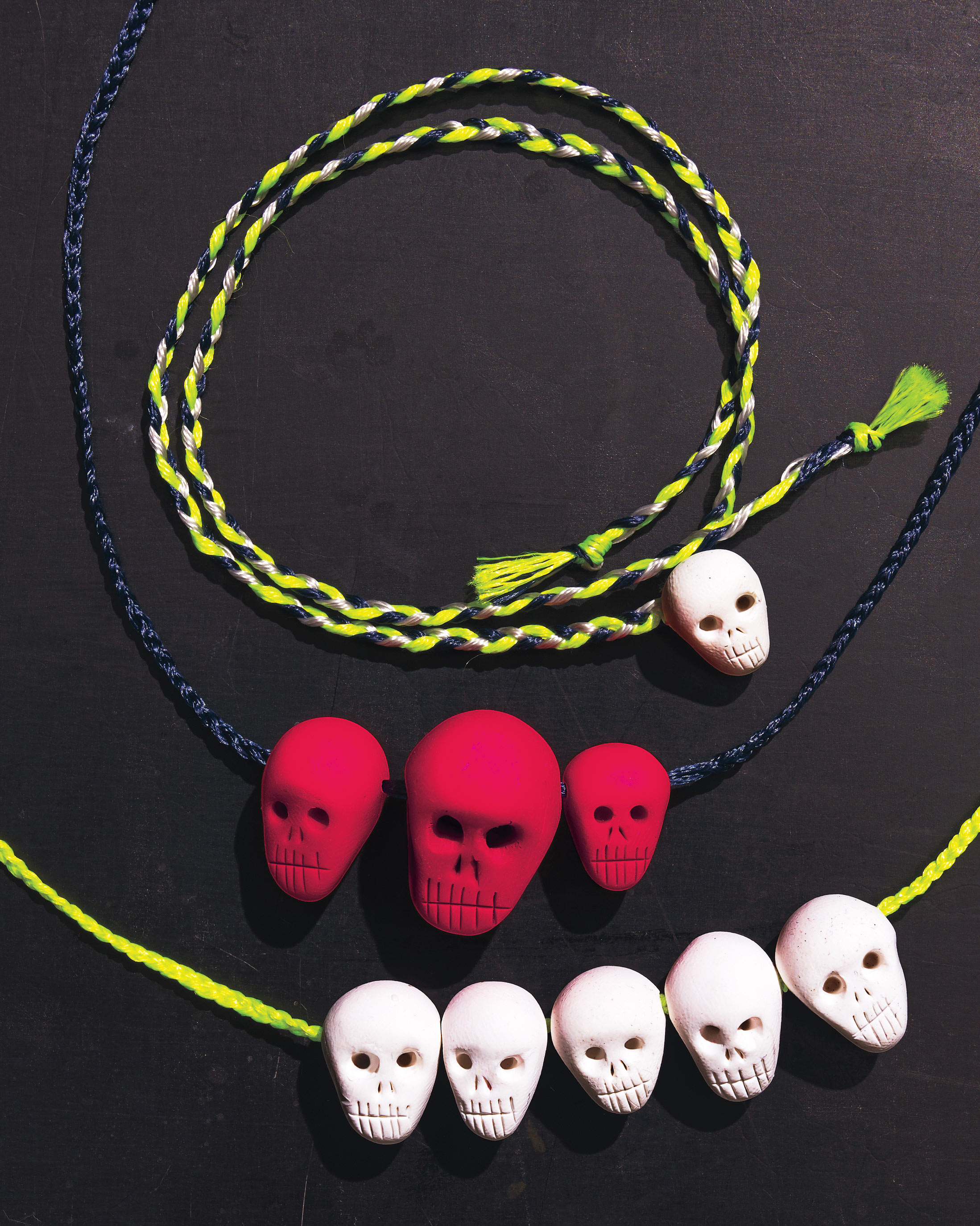 red and white skulls on braided embroidery floss necklaces
