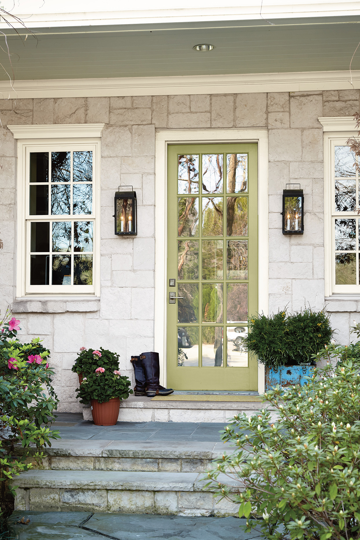 sage green front door with stone steps entrance way
