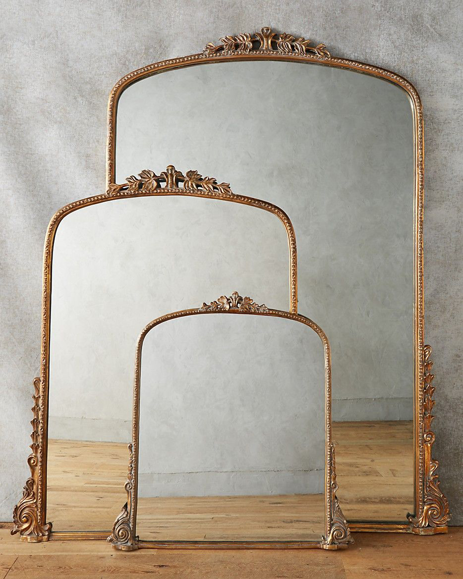 three golden framed mirrors against gray wall