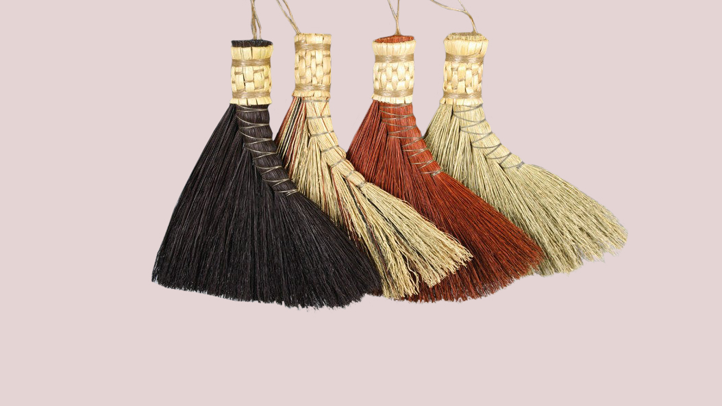 four rustic broom heads in black, tan, and red