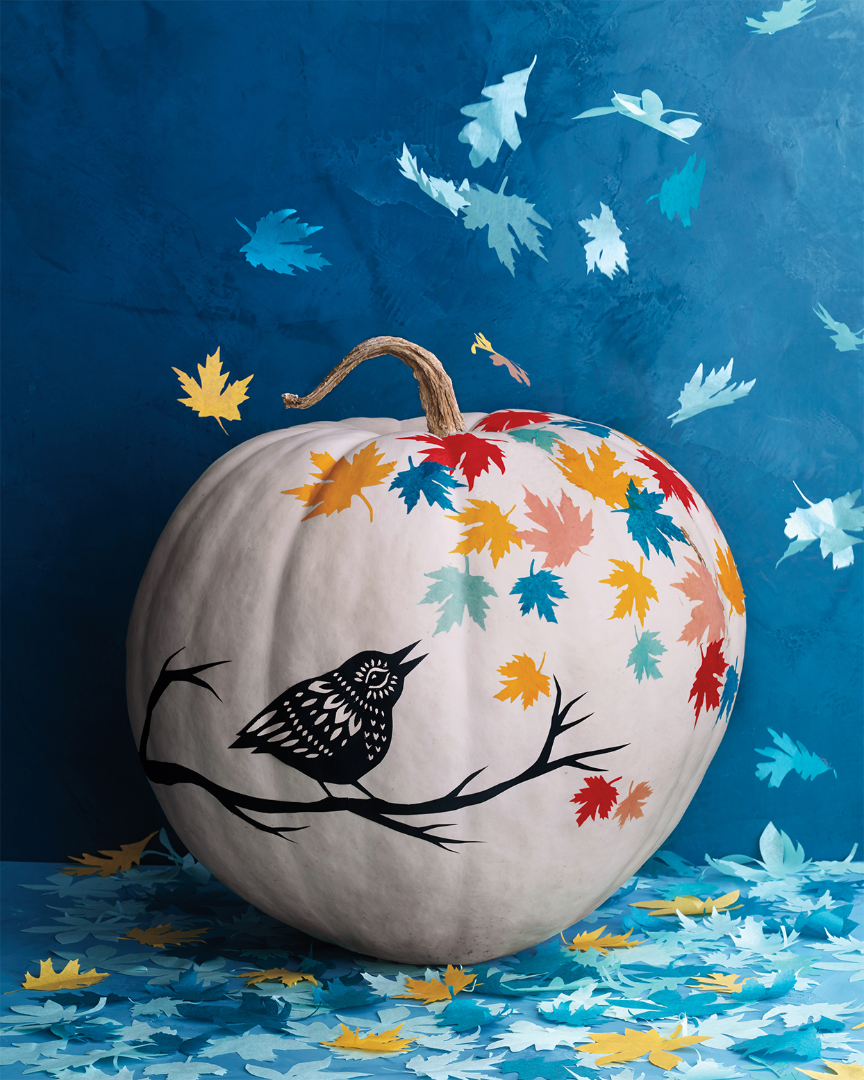 white pumpkin decorated with a bird and multi-colored leaves