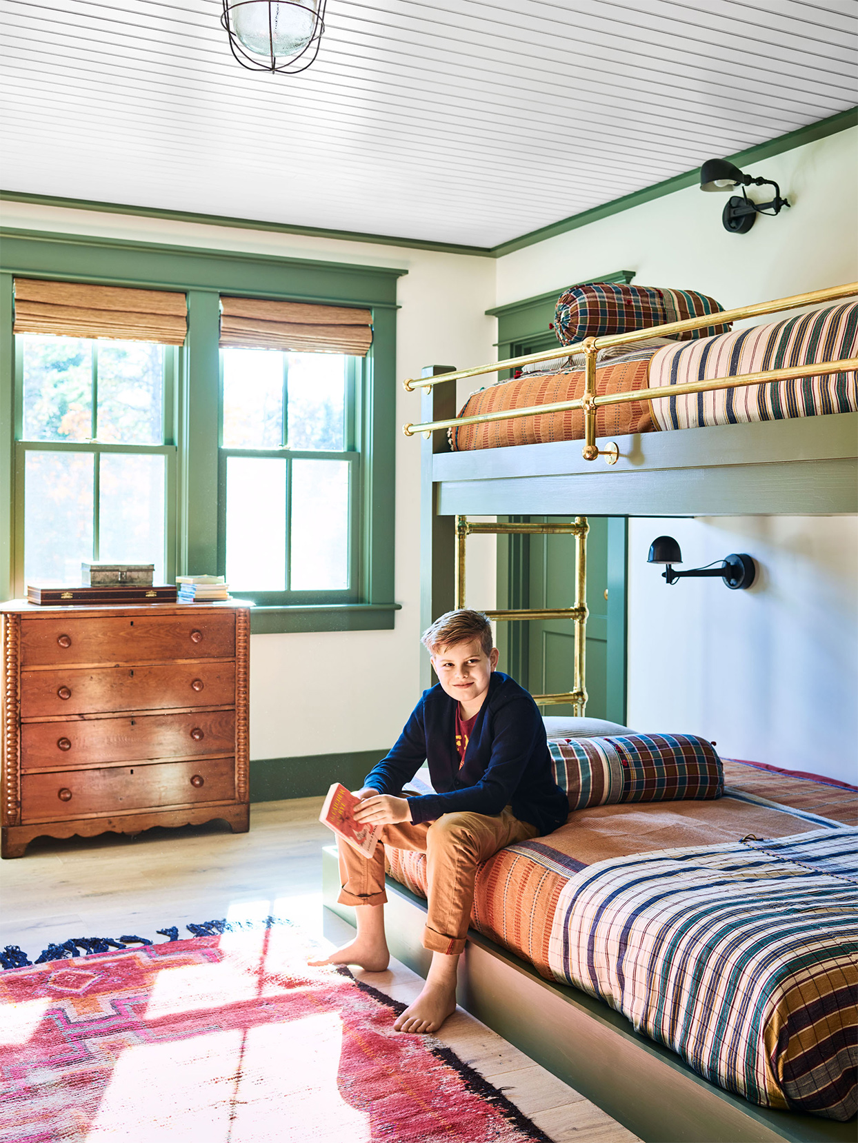 boy sits on bunk beds in cape cod home