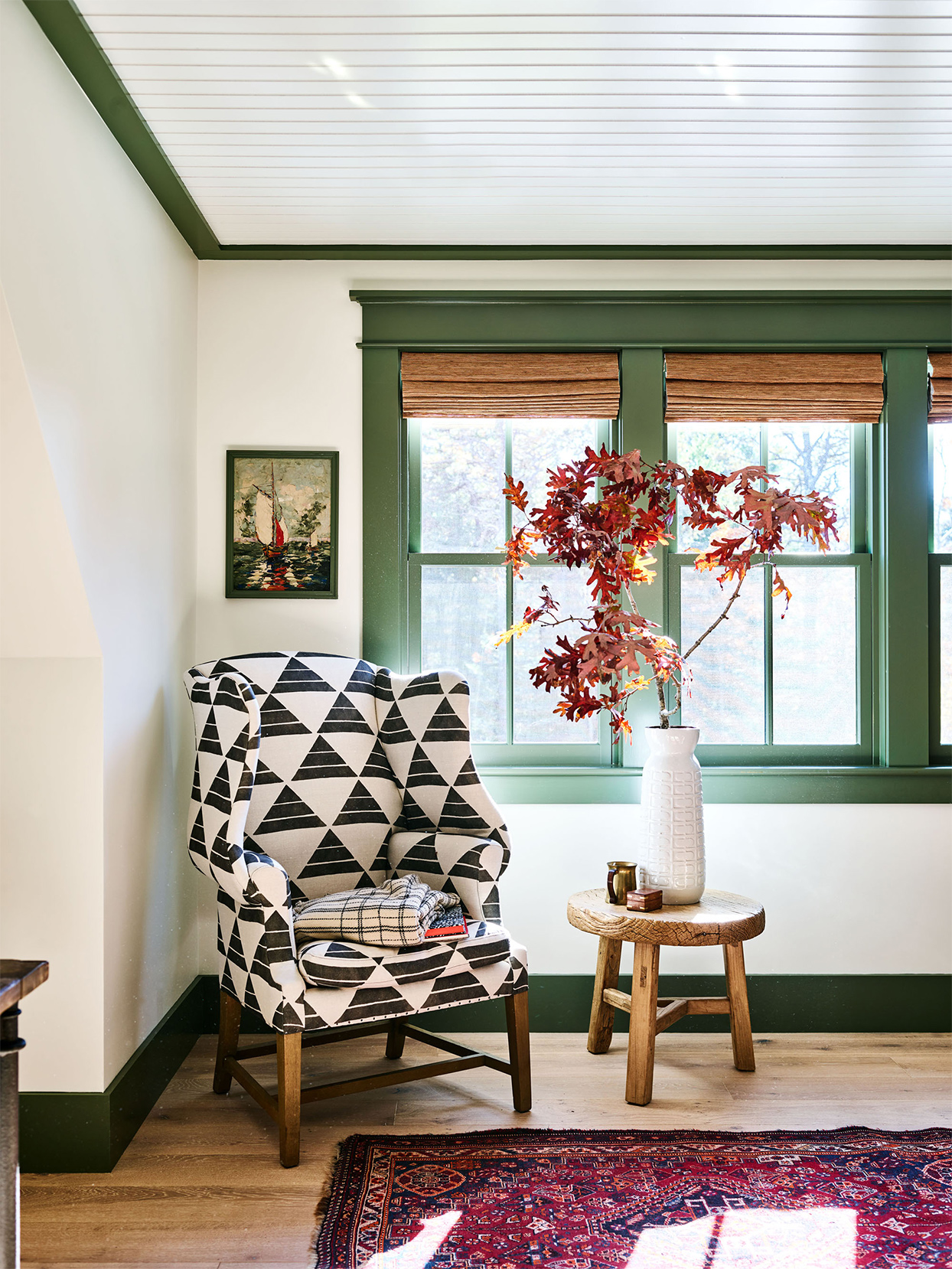 wing chair in front of green-trim window