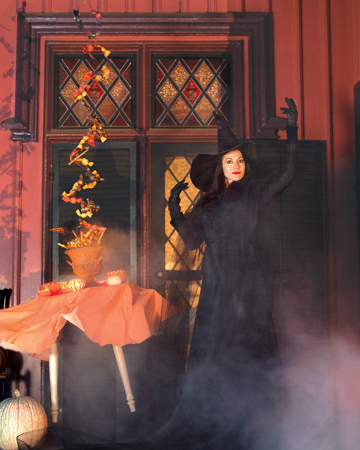 woman in witch costume next to levitating table