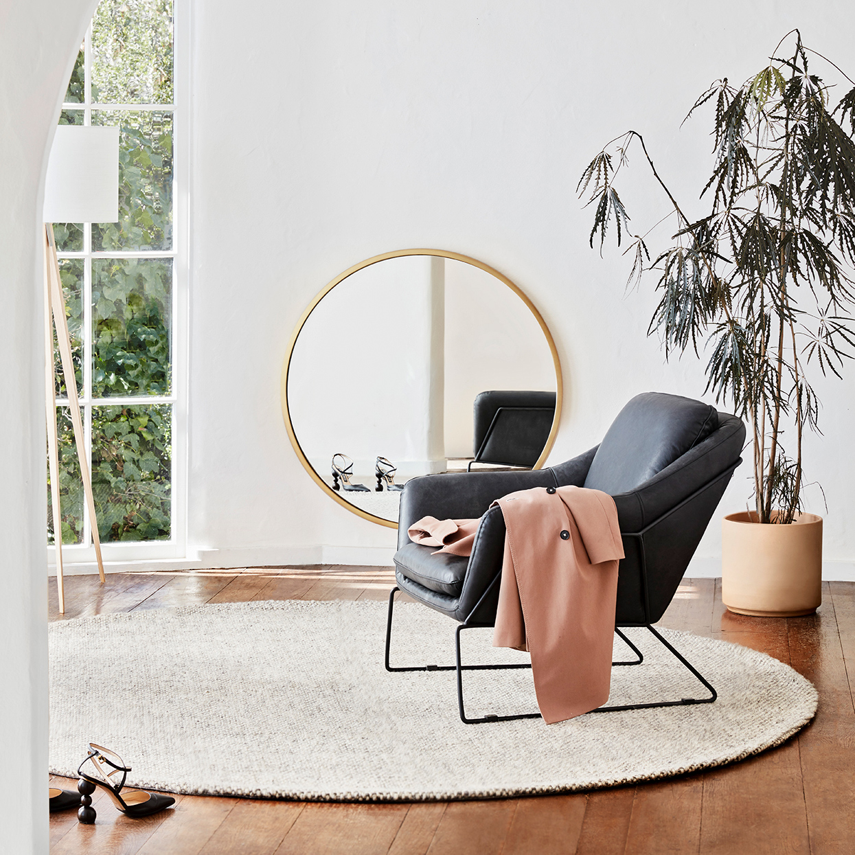 minimalist room with black chair and oversize mirror