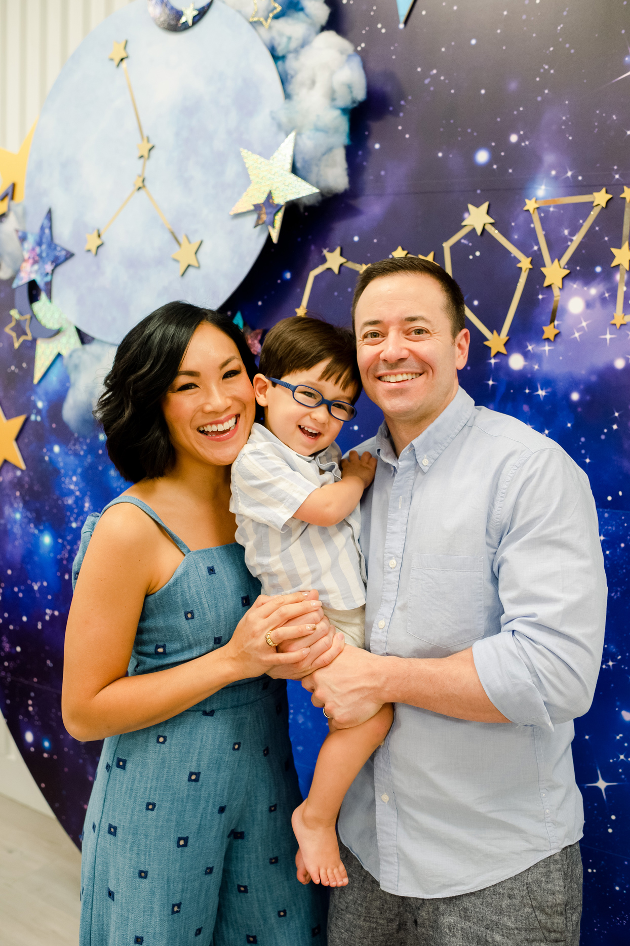 parents and kid at celestial themed birthday party smiling