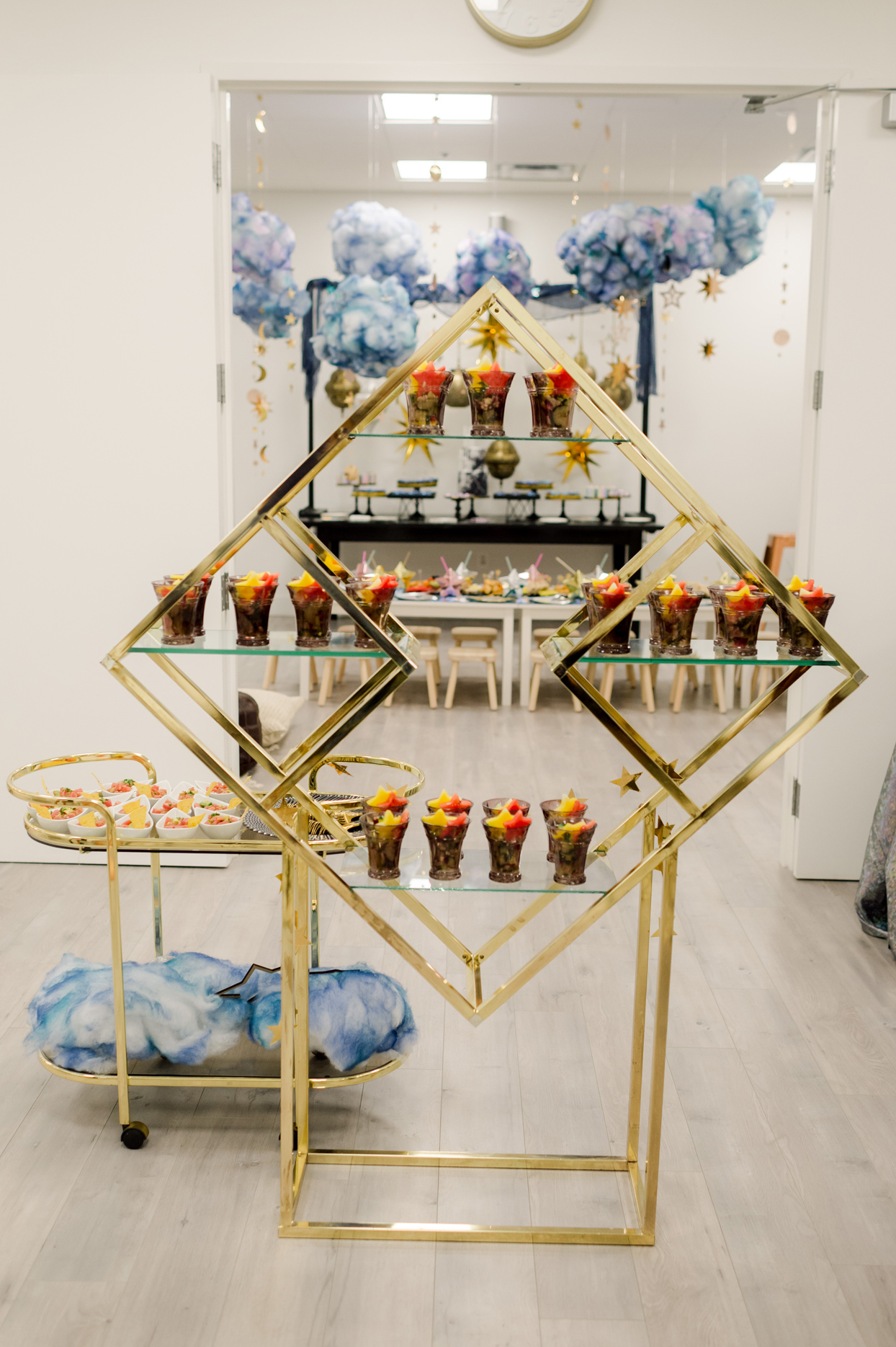 golden framed display serving table and cart with galaxy themed party snacks