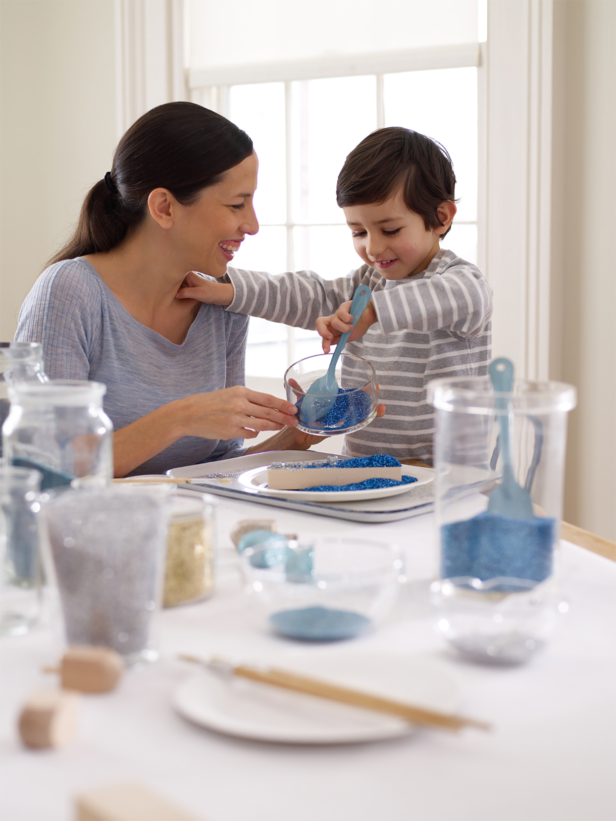 mother and son crafting with blue glitter