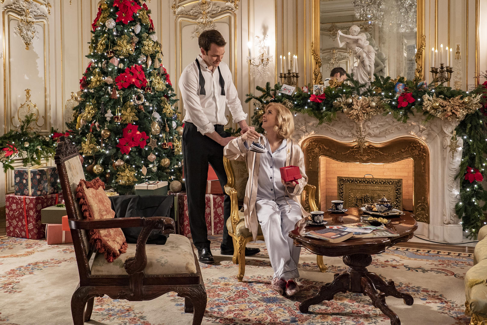 ben lamb and rose mciver in front of a christmas tree and heavily decorated mantel