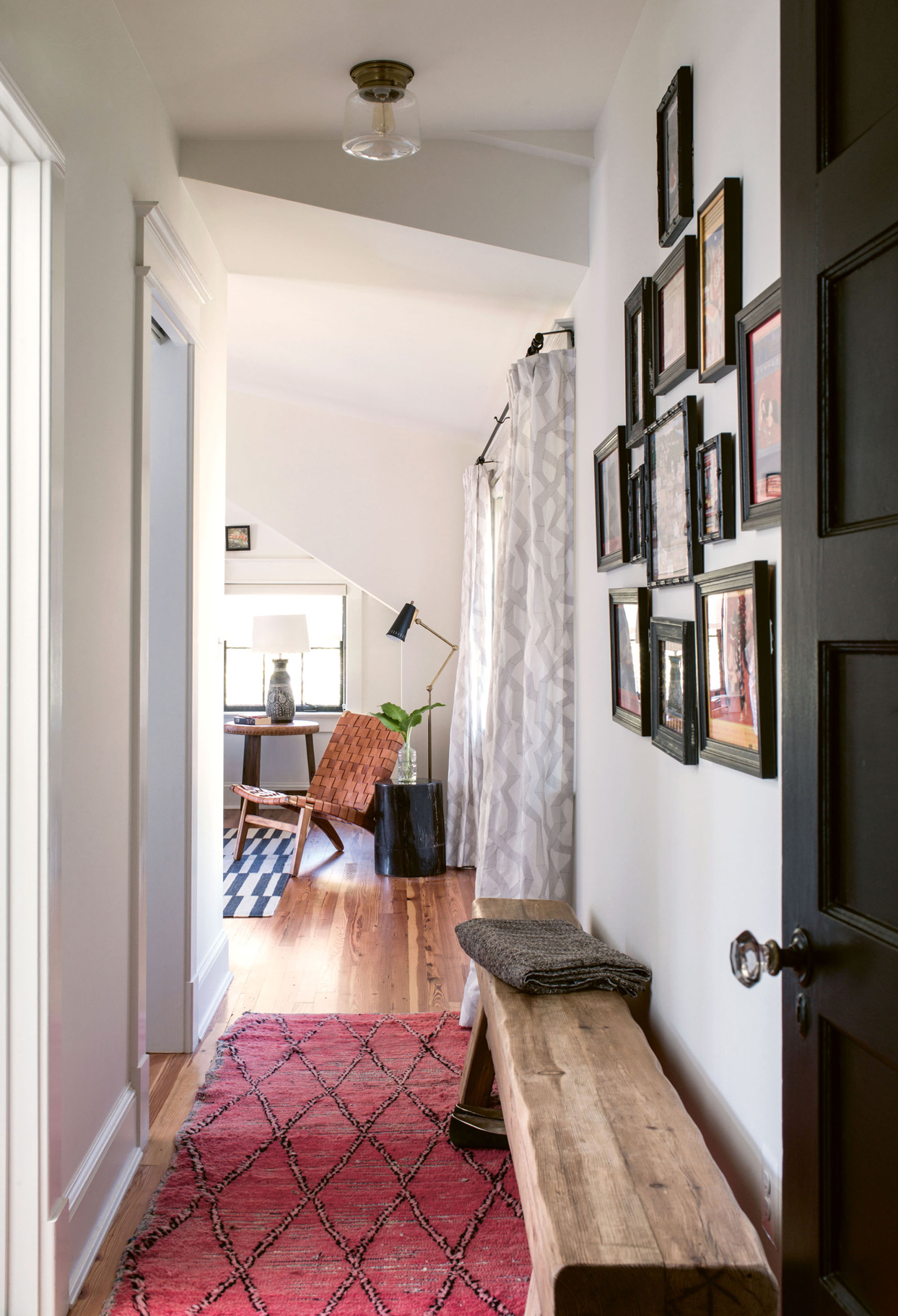 vintage bench and rug lining wide hallway