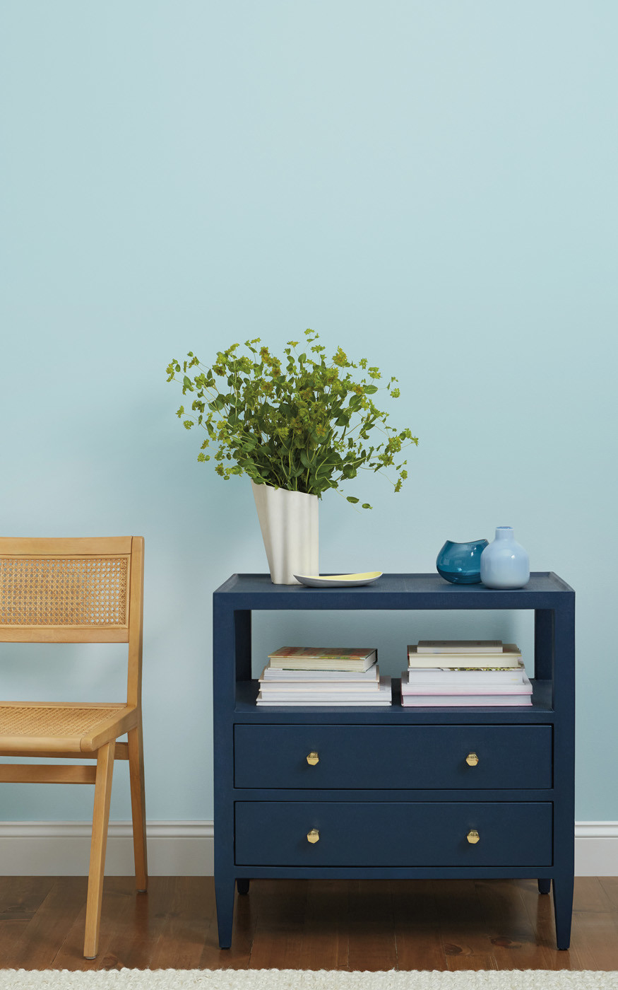 white vase of greenery atop blue book case
