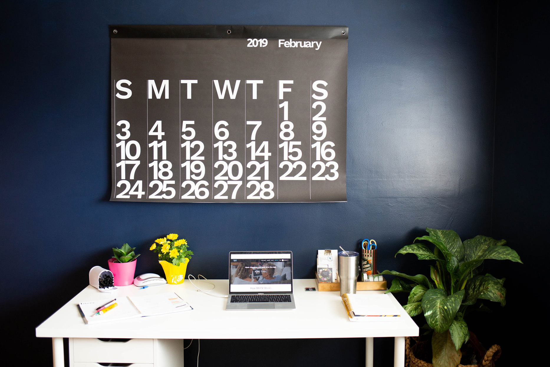 large black and white calendar hanging above white desk