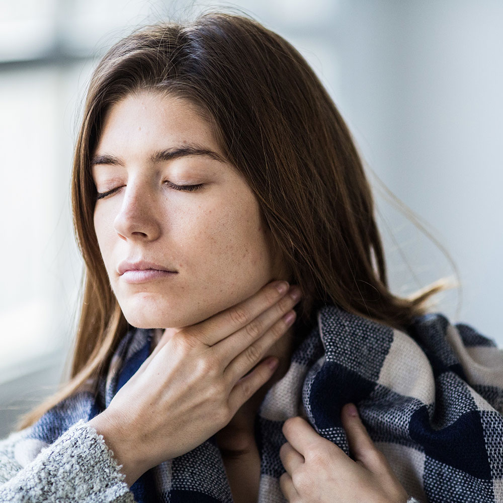 woman taking natural remedy for sore throat