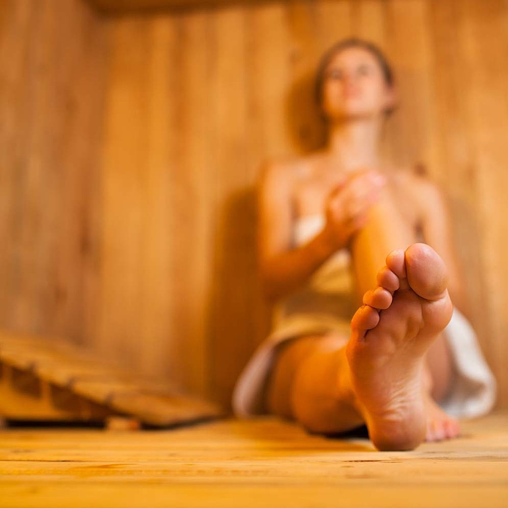 woman in a steam room to soothe sore throat naturally