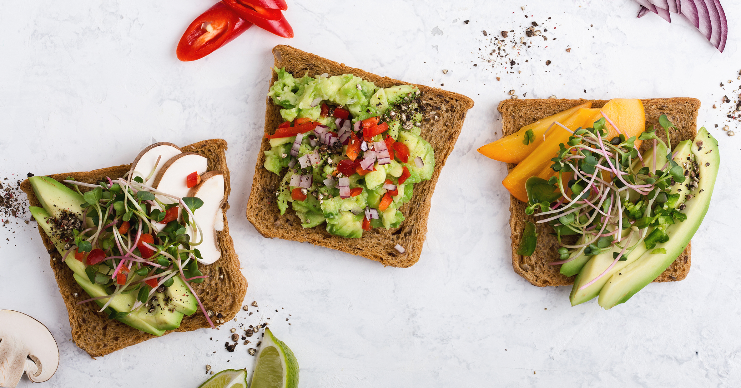 Variety of avocado toasts with fresh radish cress, mushrooms and persimmon. Plant based colorful vegan snack on gray background viewed from above
