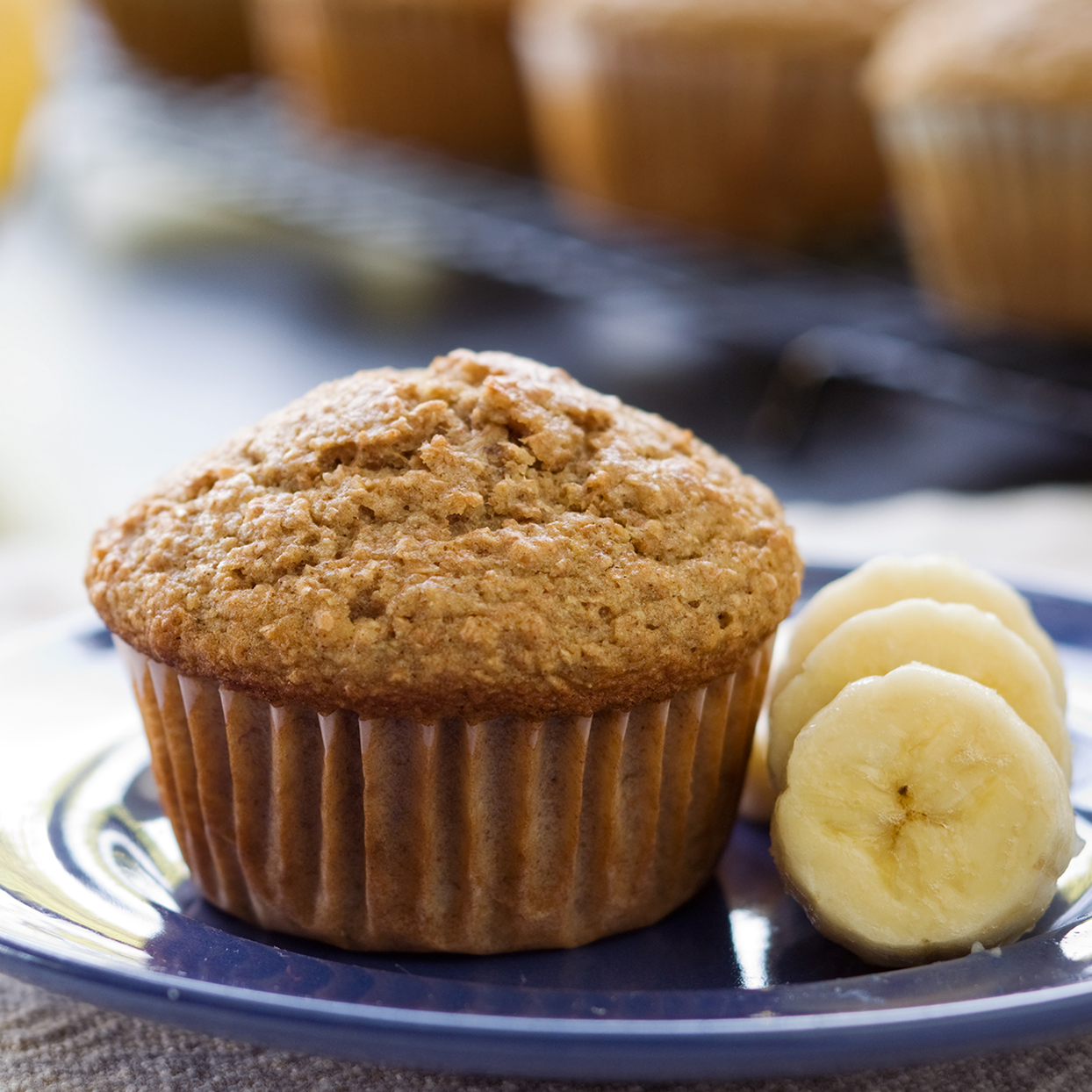 A banana bran muffin sits in front of bananas and other muffins.