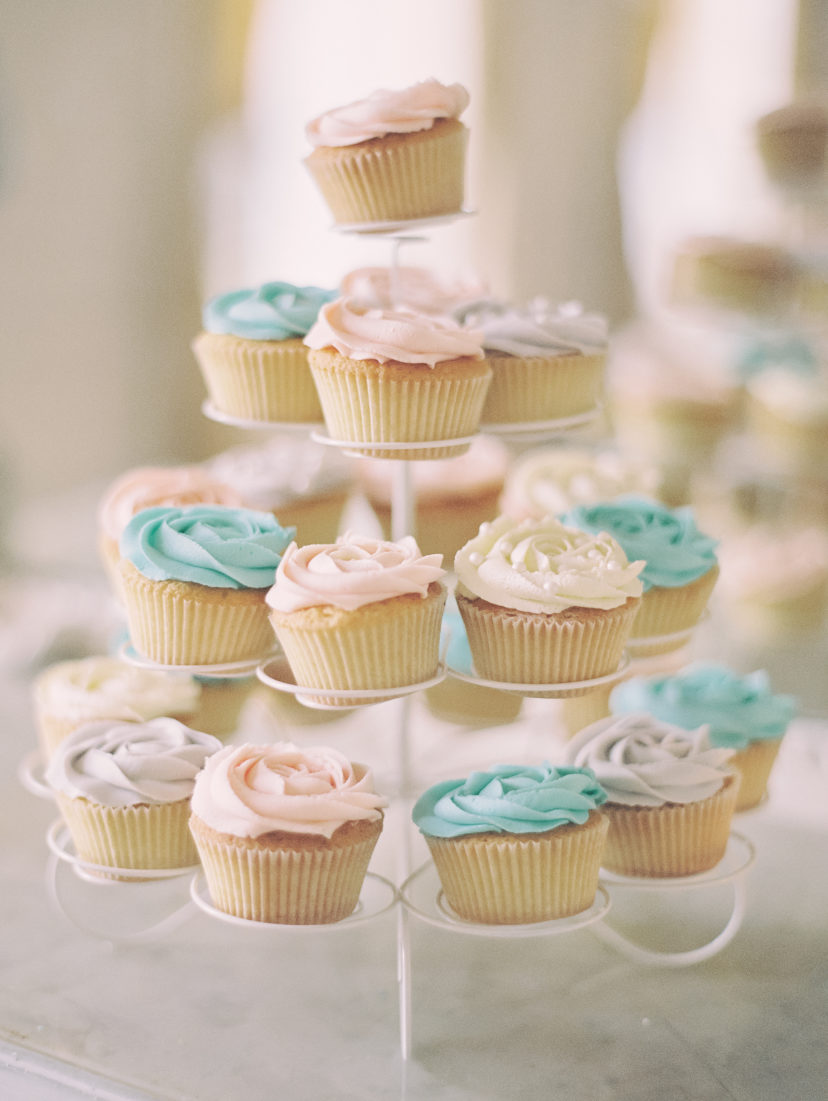 pink blue and white cupcakes on a white stand