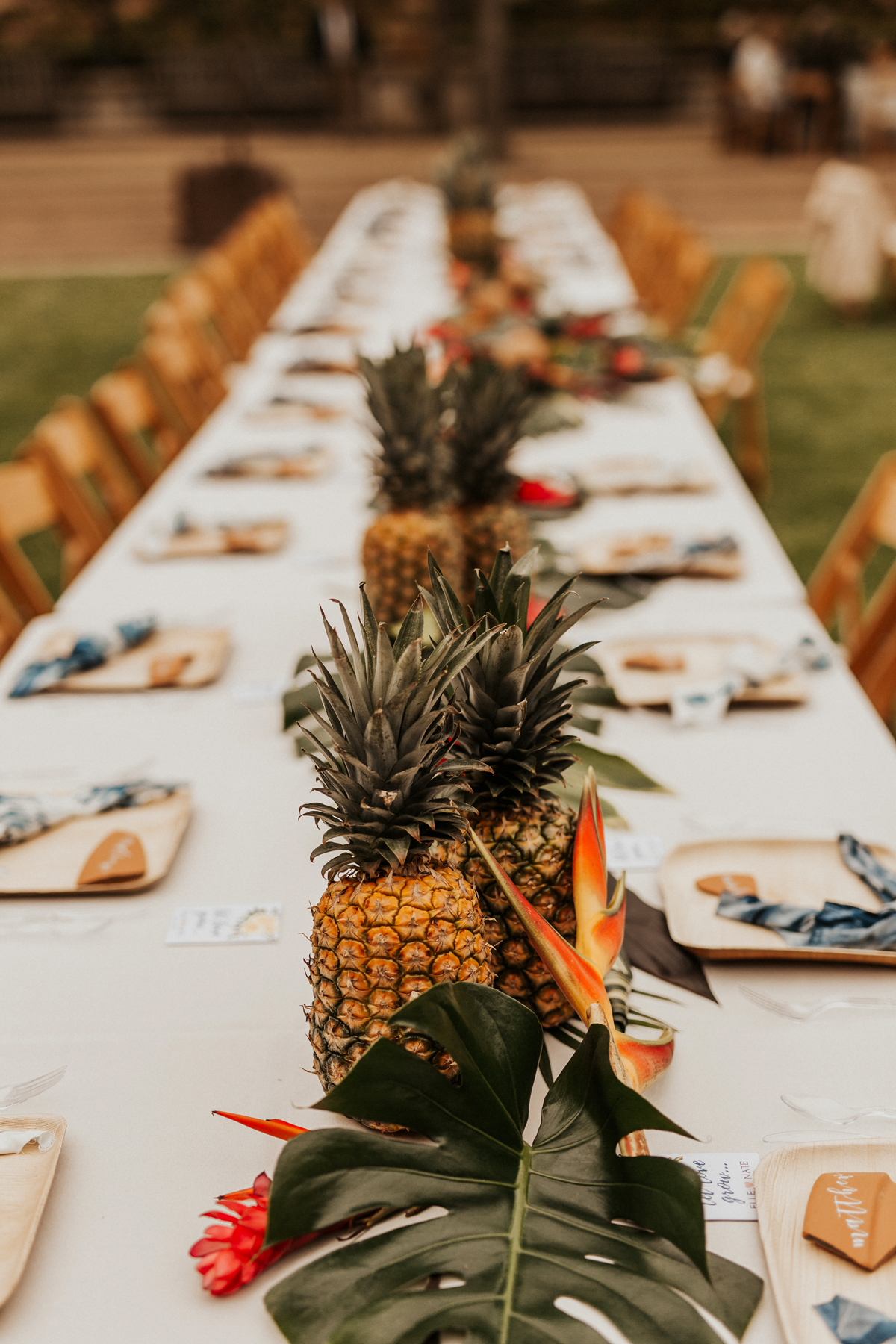 non-floral wedding centerpieces pineapples and monstera leaves