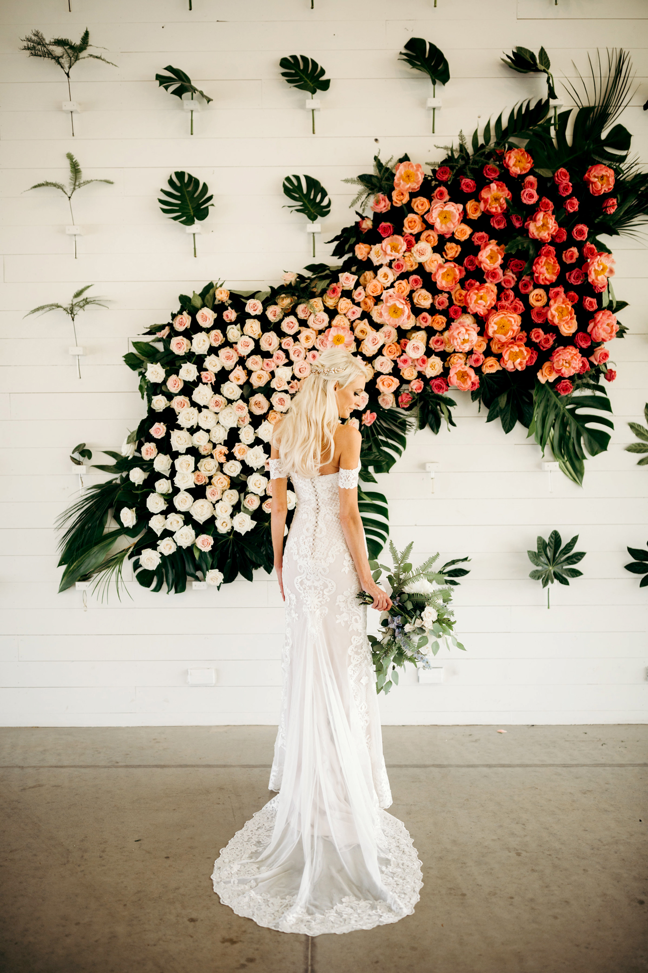 bride standing in front of orange ombre floral wall display