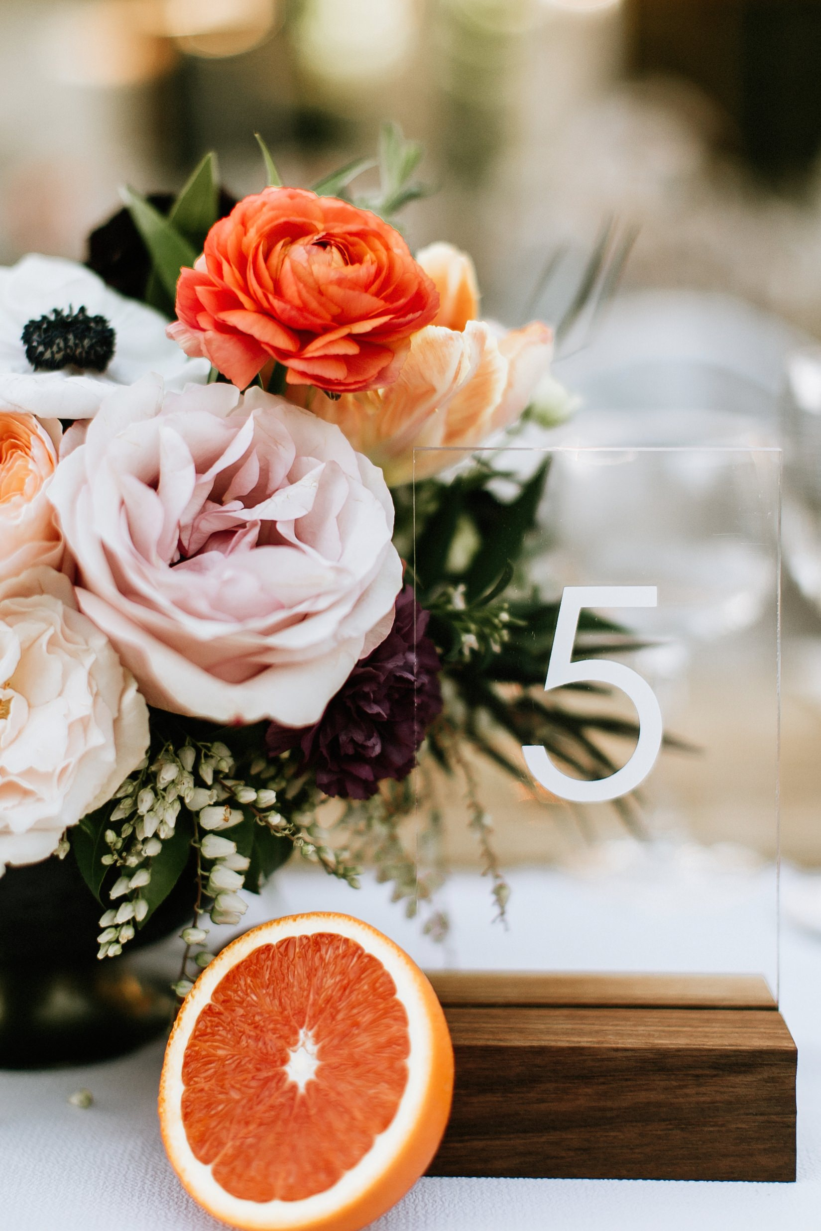 orange floral centerpiece with greenery accents
