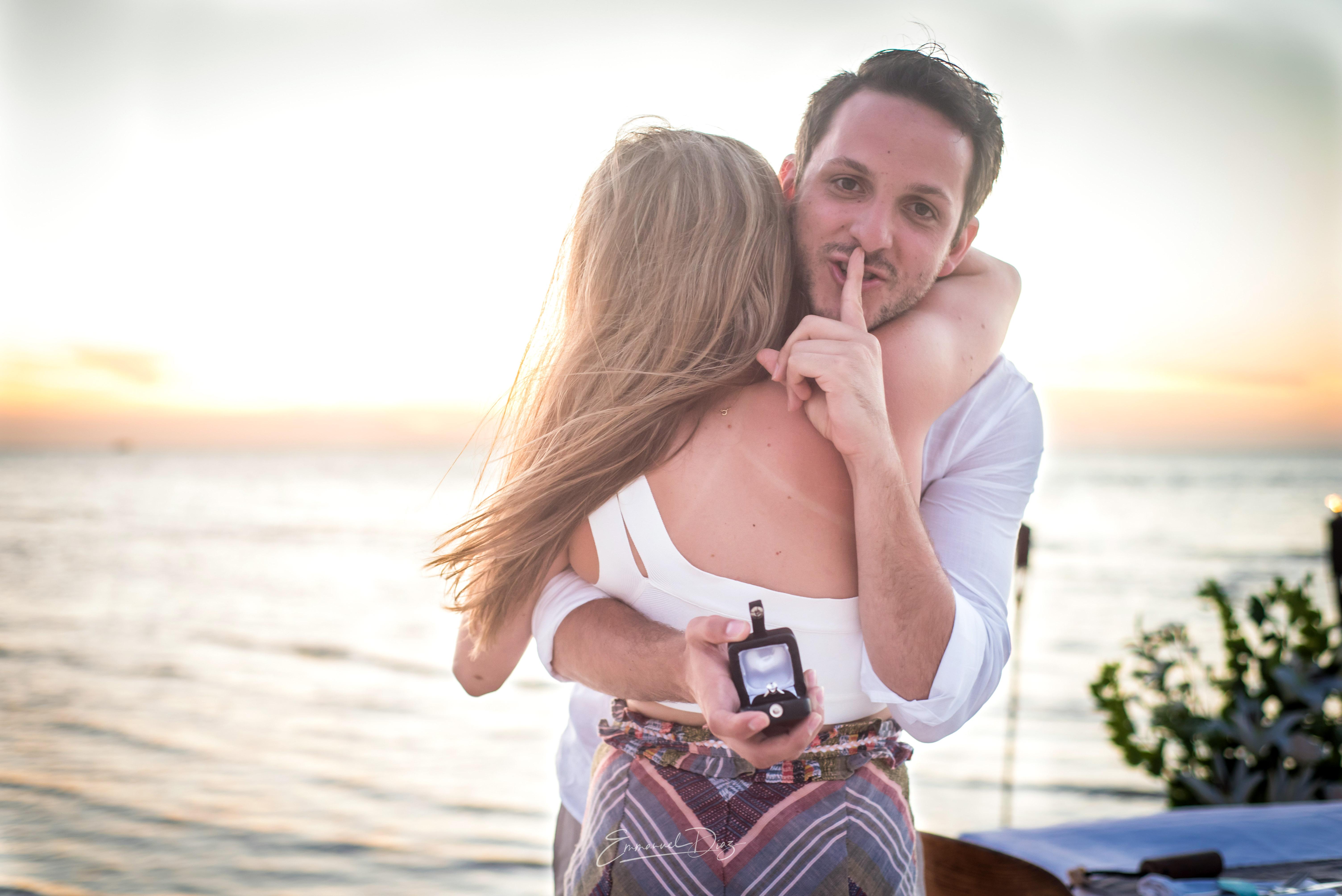 perfect proposals man hiding ring at sunset