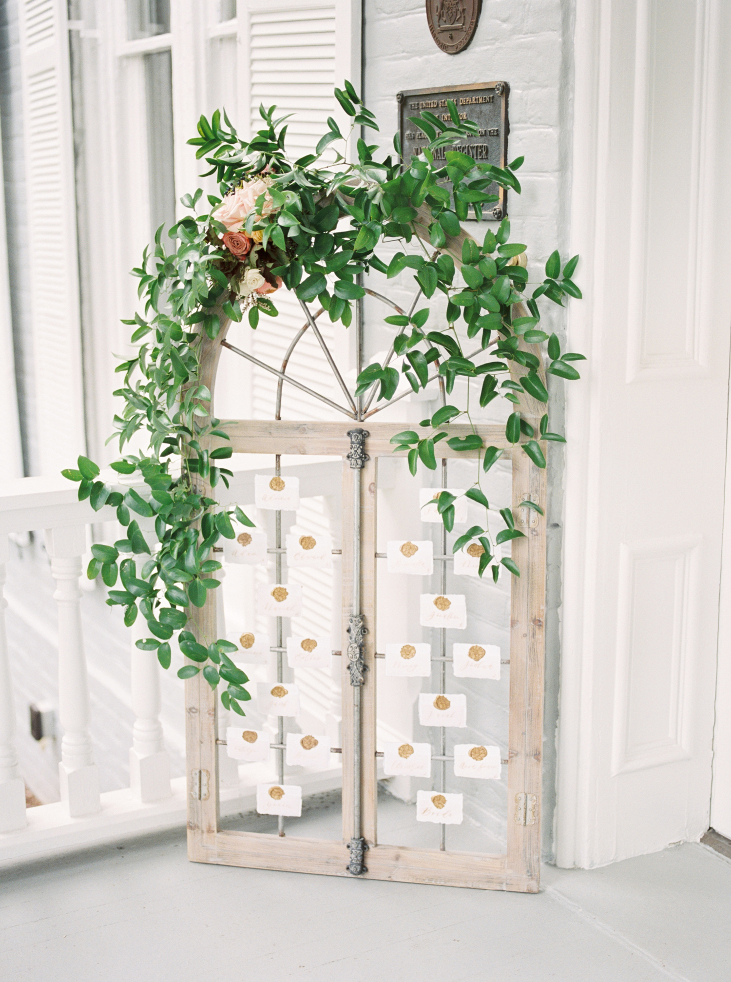 greenery garland arched above seating chart