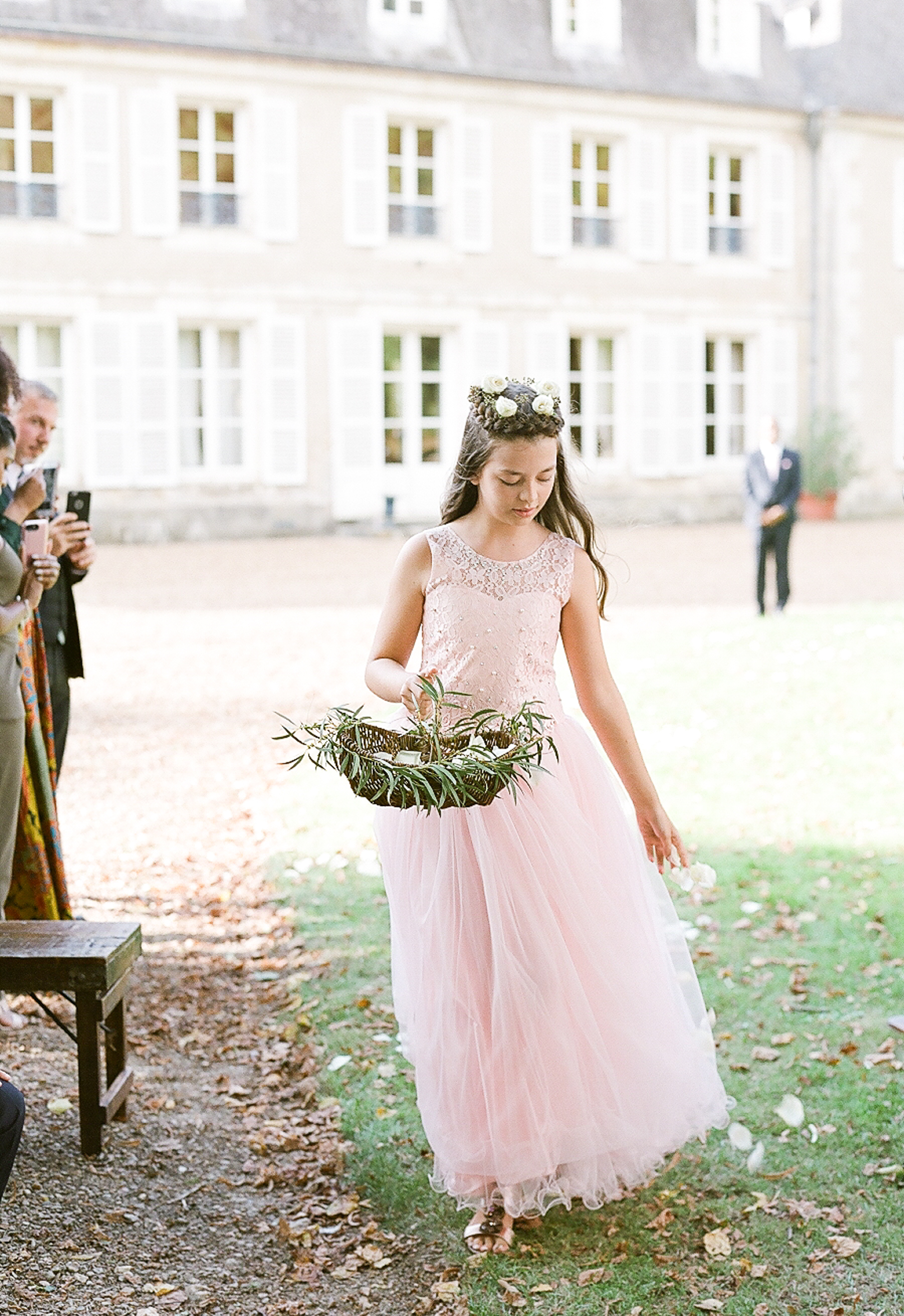 flower girl holding brown wicker basket with greenery
