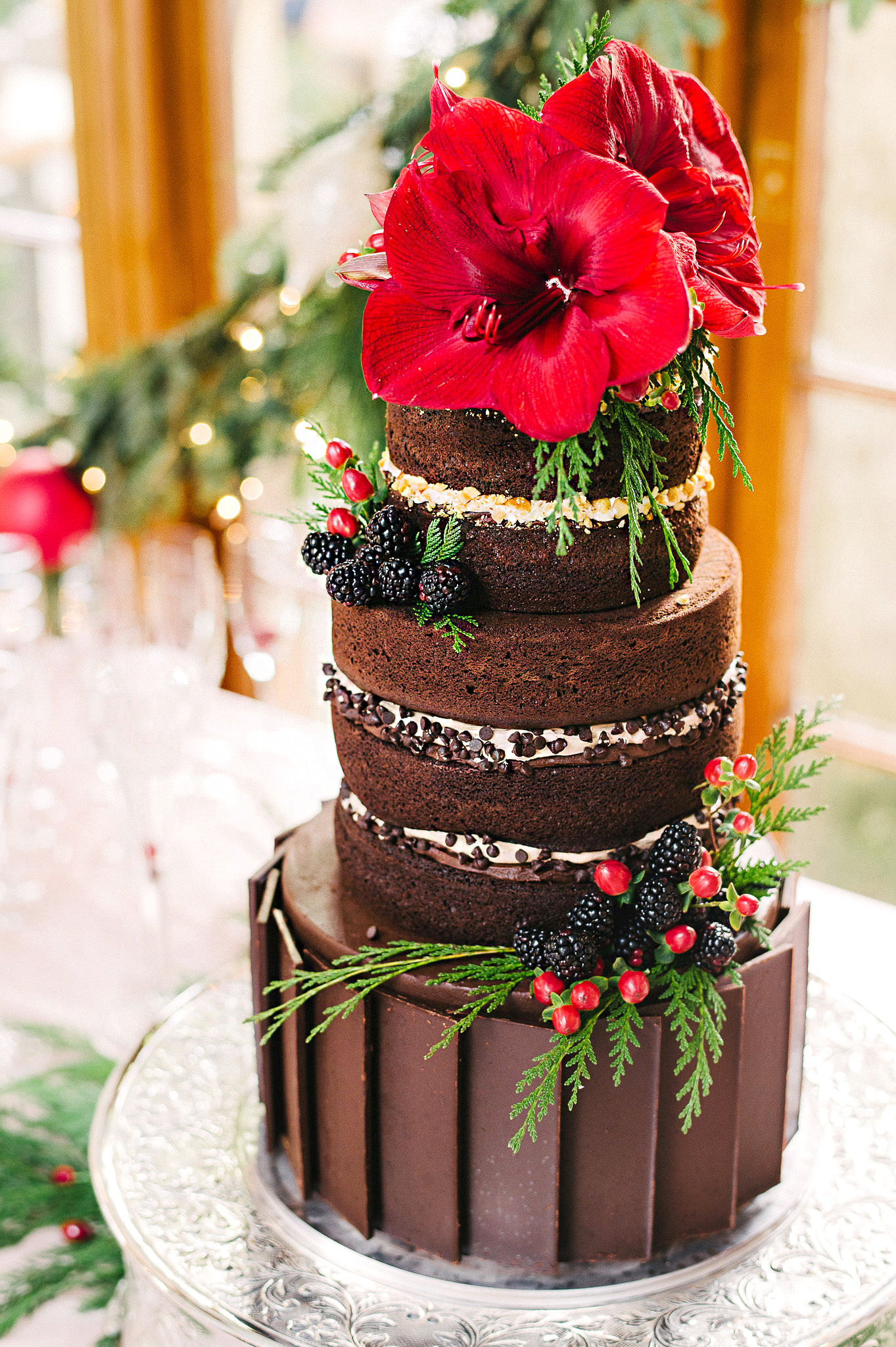 tall chocolate cake with blooms and berries