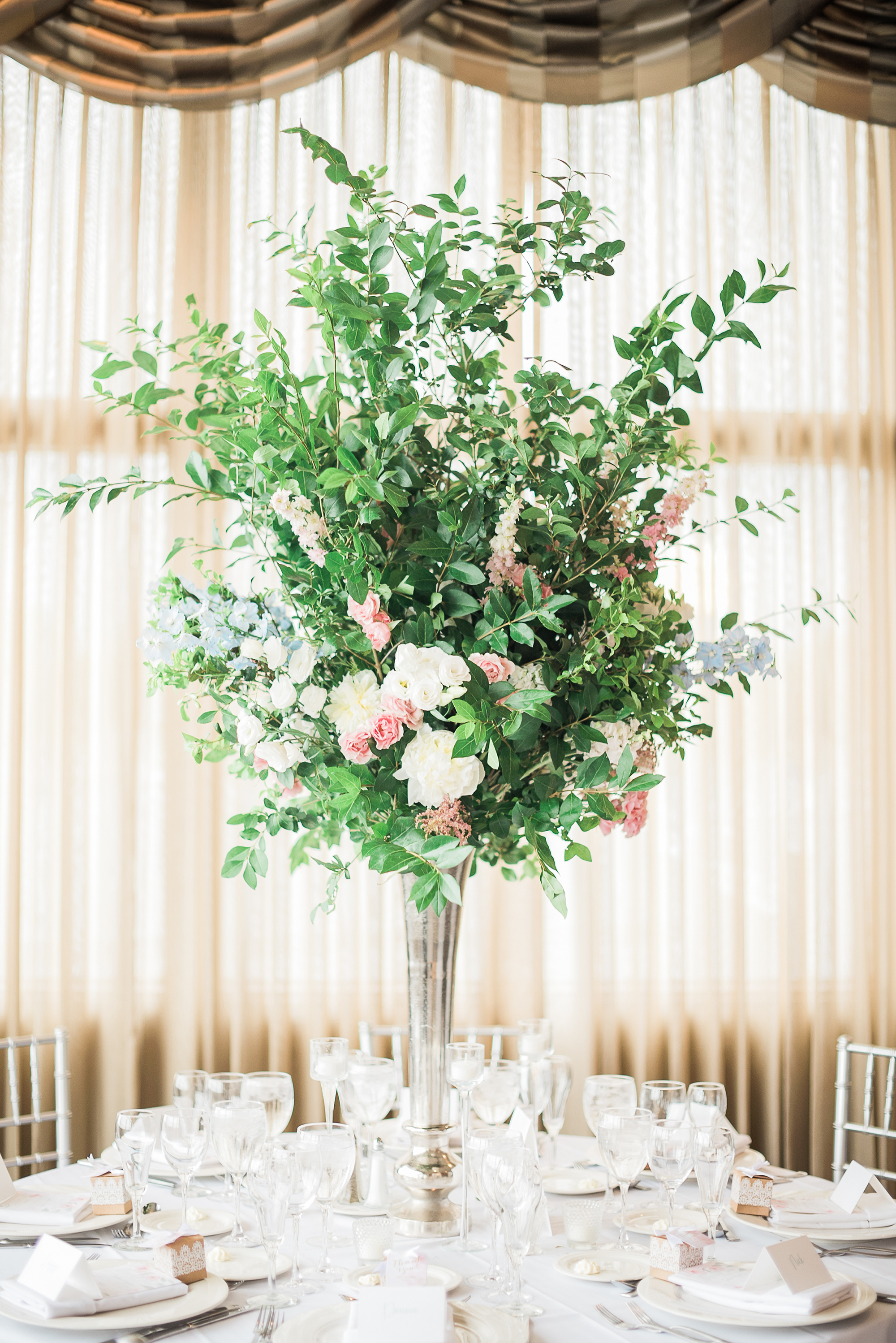 tall centerpiece with greenery and garden roses