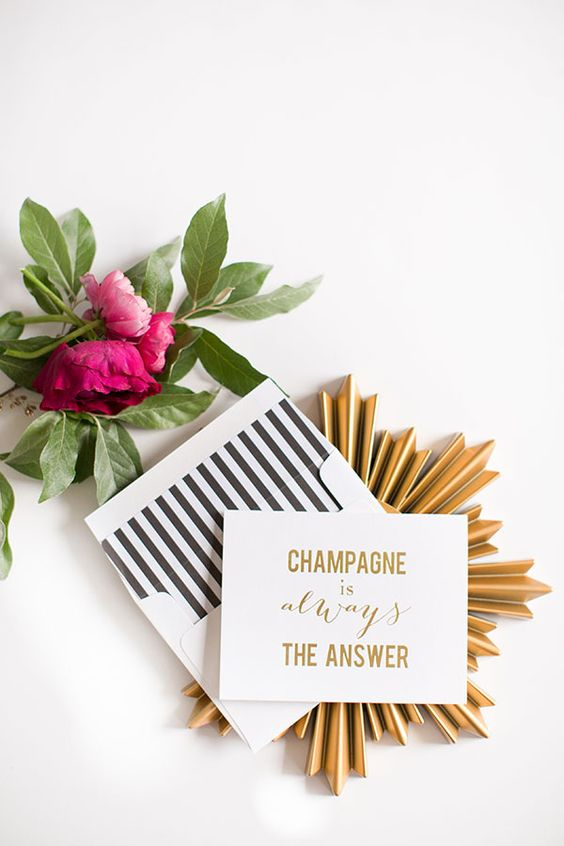 "white cardstock invites with gold writing ""Champagne is always the answer"""