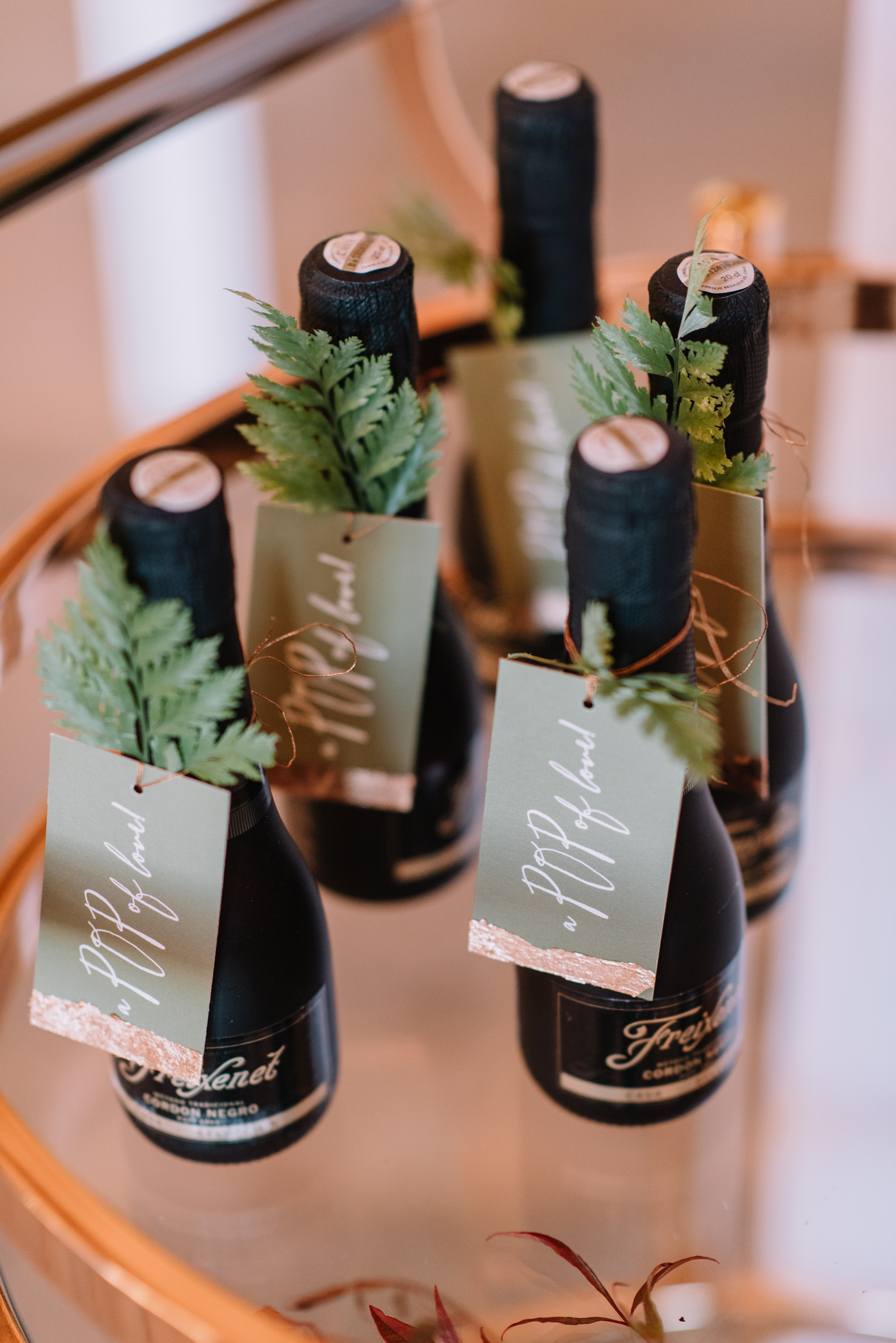 mini champagne bottle wedding favors with fern leaf name tag decor