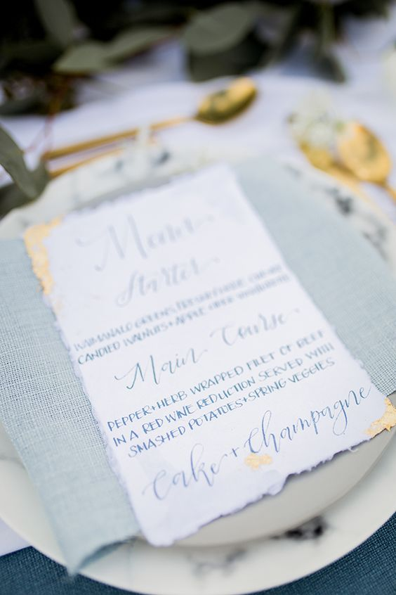 raw edge white stationary menu with navy calligraphy and gold foil accents