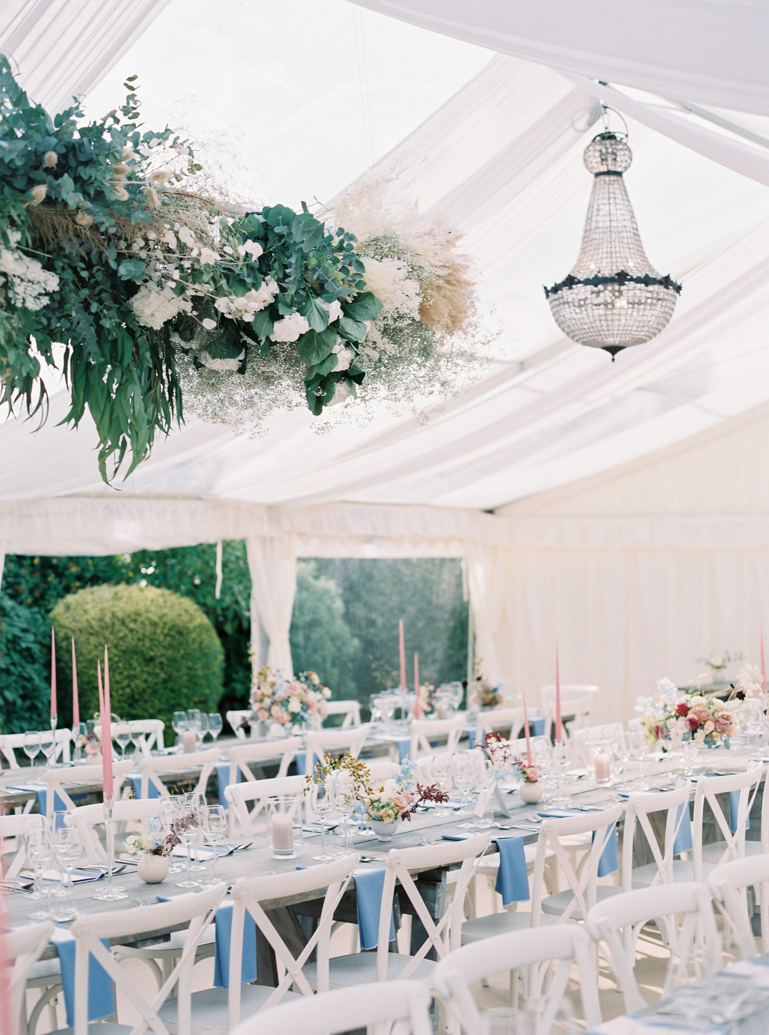 tented reception with long wooden tables, white chairs, chandeliers, and hanging floral arrangements